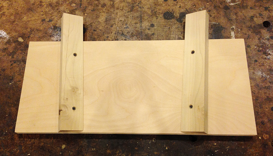 After laying out the correct angles, two support block are attached to the base along the angled lines with screws