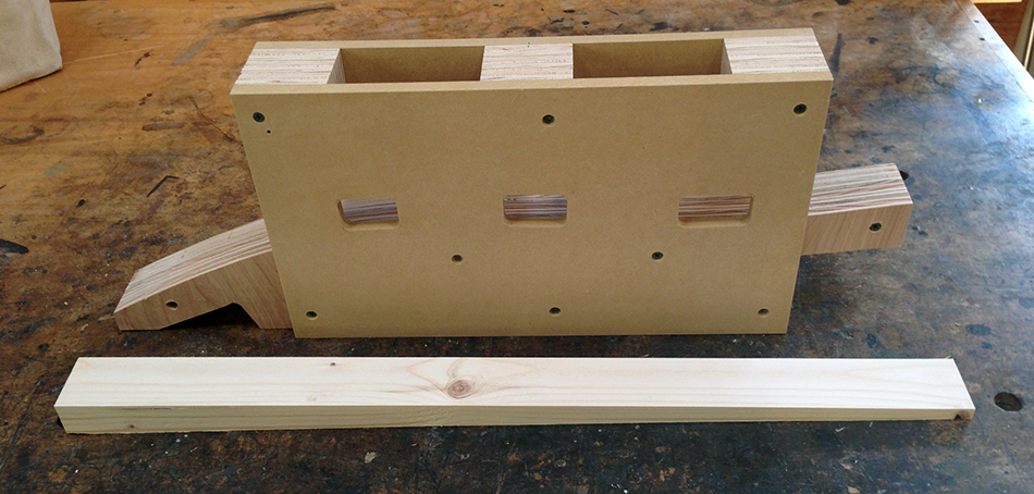 The finished slat mortising jig along with a wedge that supports the rear leg