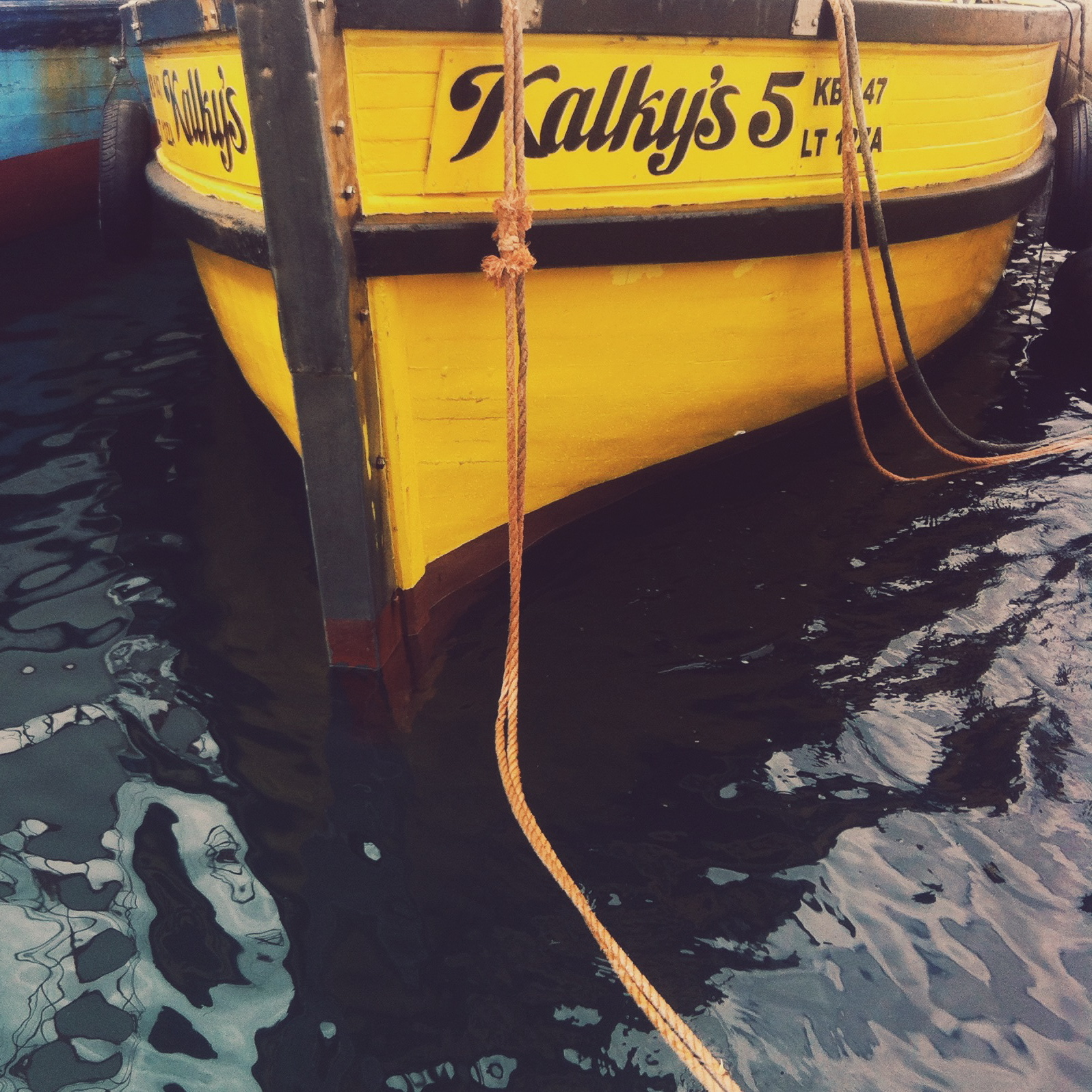 One of the many brightly painted fishing boats docked at the Kalk Bay harbour.