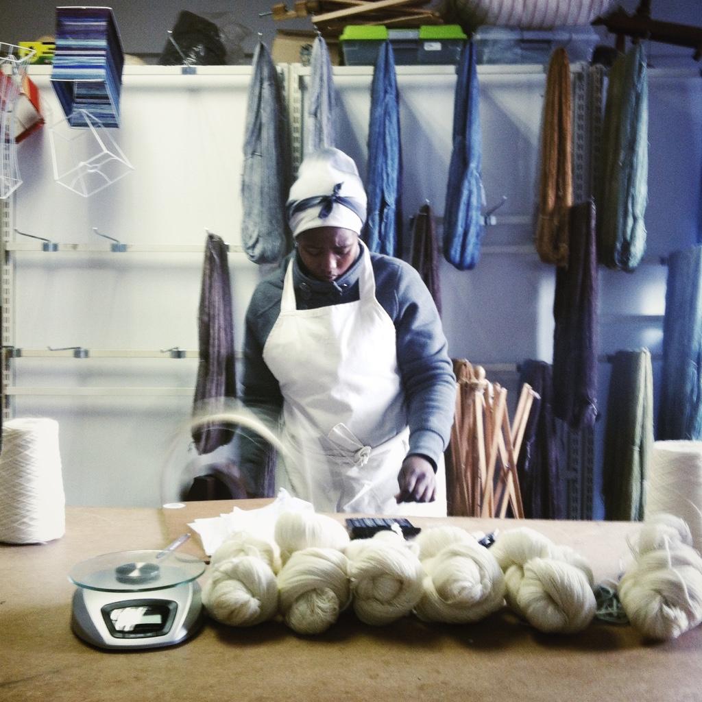 Julia weighing and packaging wool in the workshop.