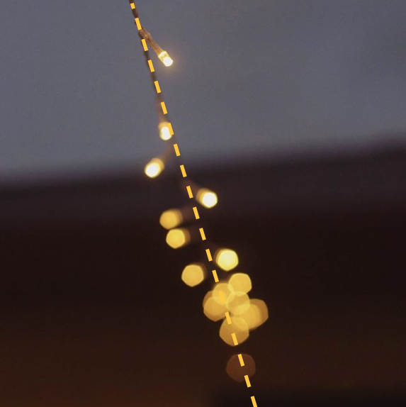 This string of fairy lights cut at an angle through this image.
