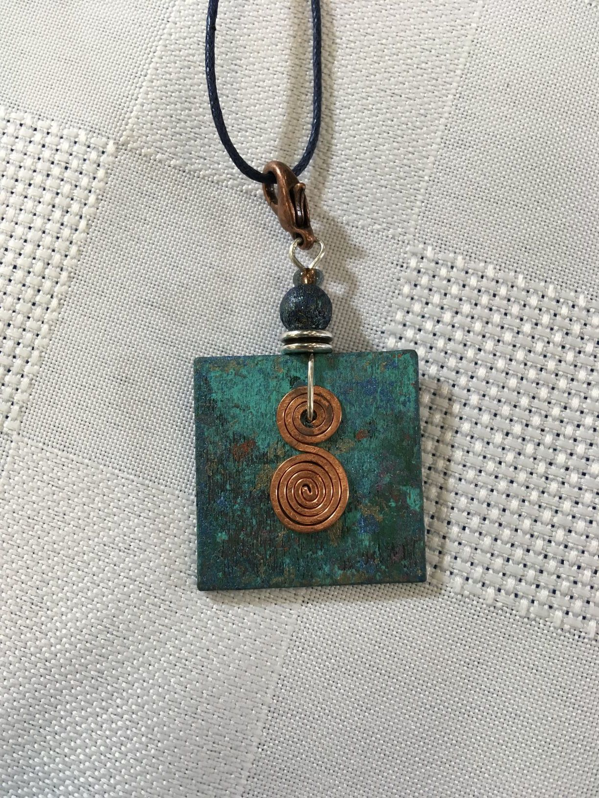 Rachel Joy VanRooyen, #3, square turquoise coloured wooden pendant with hammered copper accent.JPG