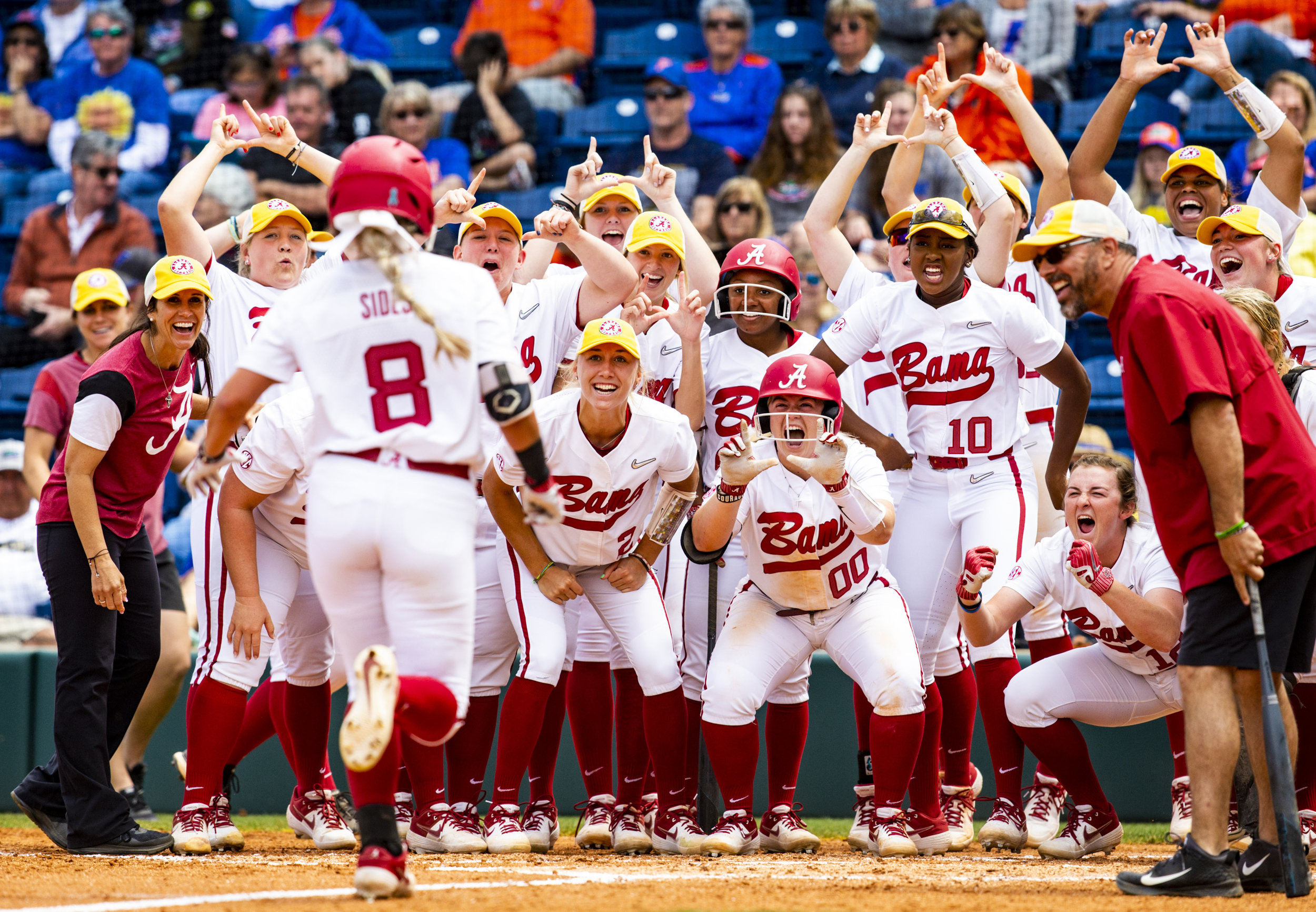 Alabama Crimson Tide outfielder KB Sides' (8) teammates celebrate as Sides comes in to score after hitting a home run during the Florida Gators home game against the Alabama Crimson Tide on April 20, 2019. The Gators lost 3-0 to the Crimson Tide.