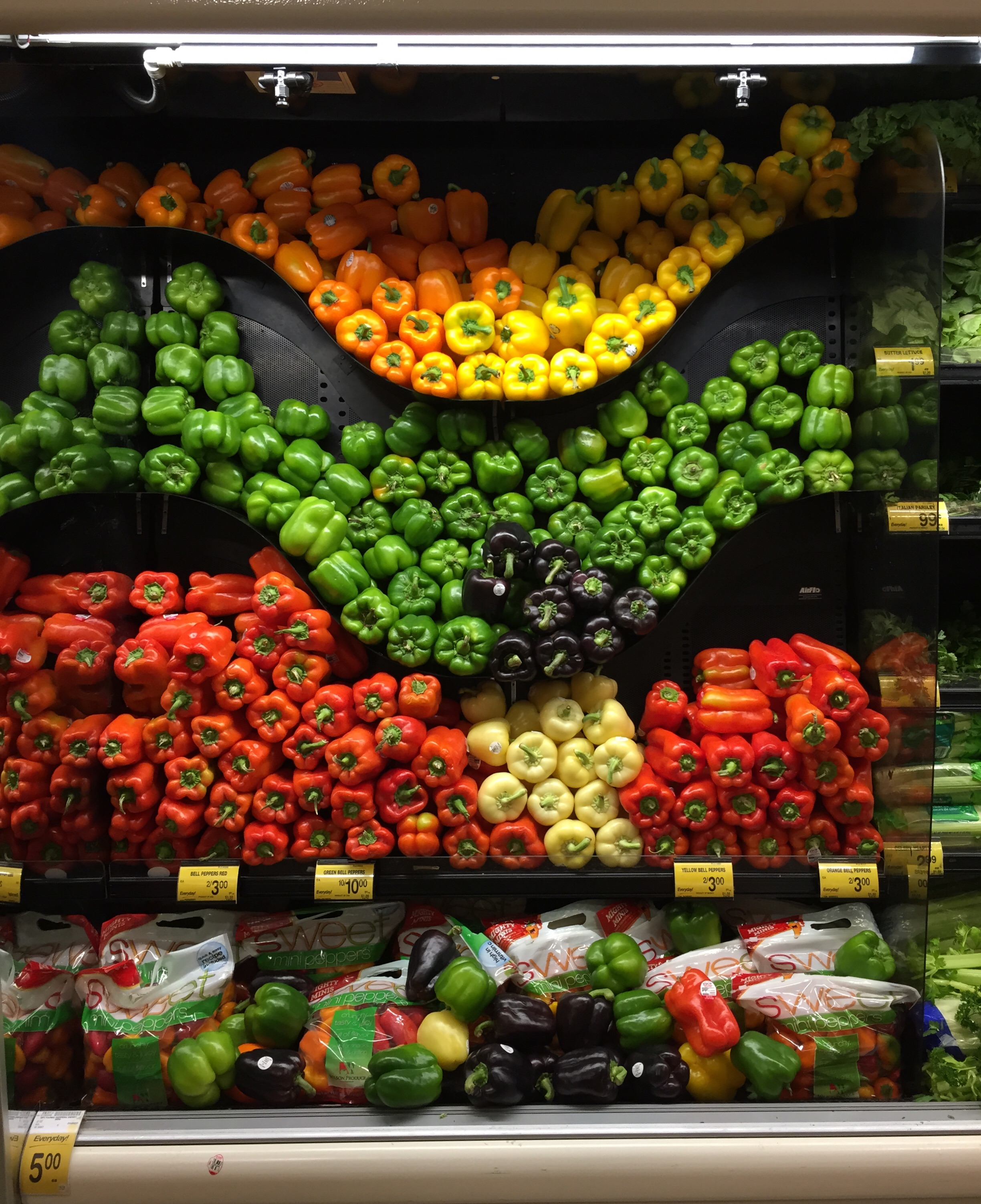 """This is how peppers were set up at Safeway. Notice the line of peppers layering the bottom. I Tweeted """"@Safeway How am I supposed to get my peppers?"""" The response was almost instant asking which location this was at."""