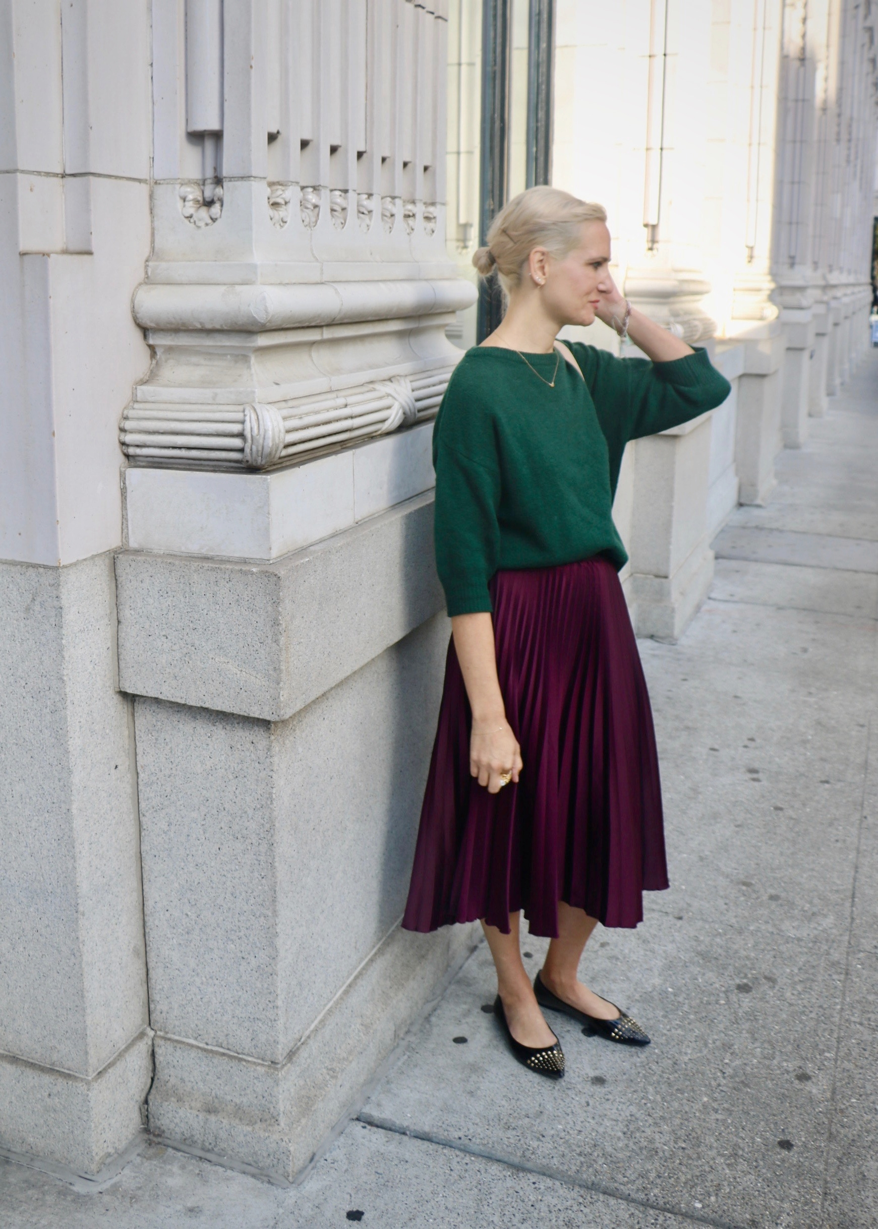 Outfit details: H&M pleated midi skirt ( similar ), green crop sweater ( similar ), patent leather studded flats ( similar ),  Cuyana circle crossbody