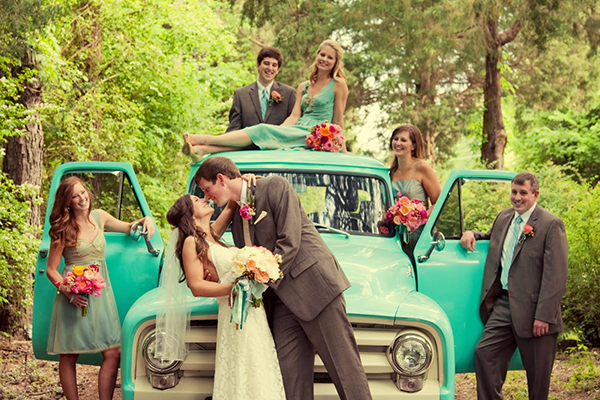 bridal-party-gathers-on-an-old-teal-truck-to-watch-the-bride-kiss-her-groom.jpg