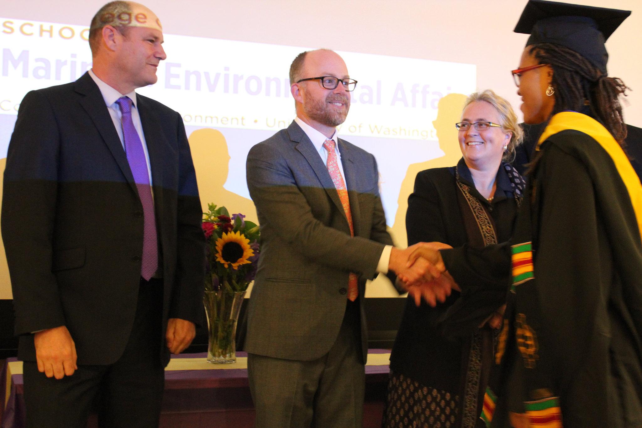 Jillian Lyles shakes Professor Kelly's hand as Professor Dolsak and Professor Allison look on.