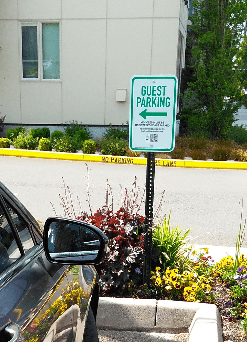 A guest parking sign with a barcode directing gueststo register a digital parking permit.