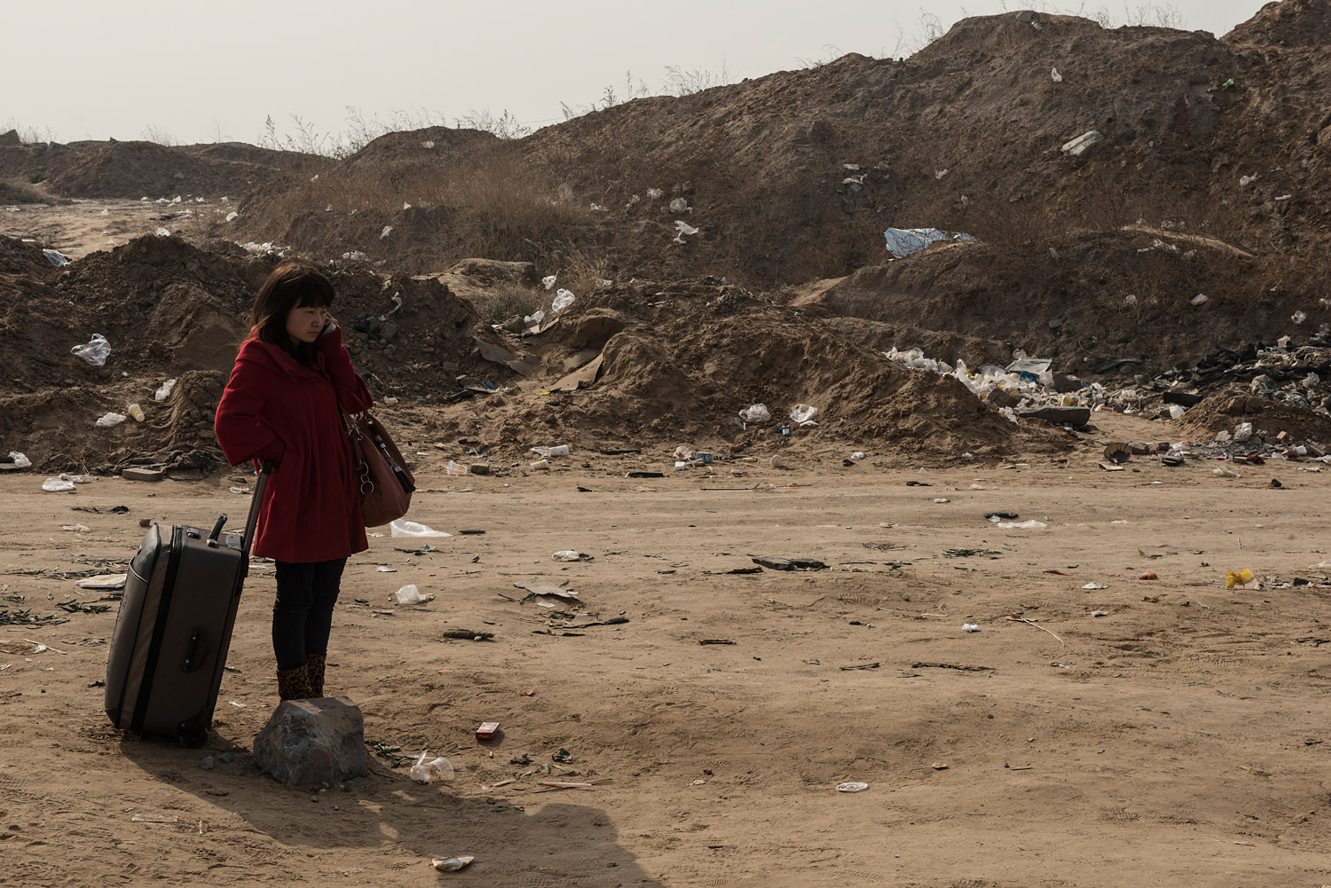 A woman has just arrived for a visit at Foxconn factory city on the outskirts of Zhengzhou. She is calling her boyfriend working on an I-phone assembly line. She might join the workers' ranks.