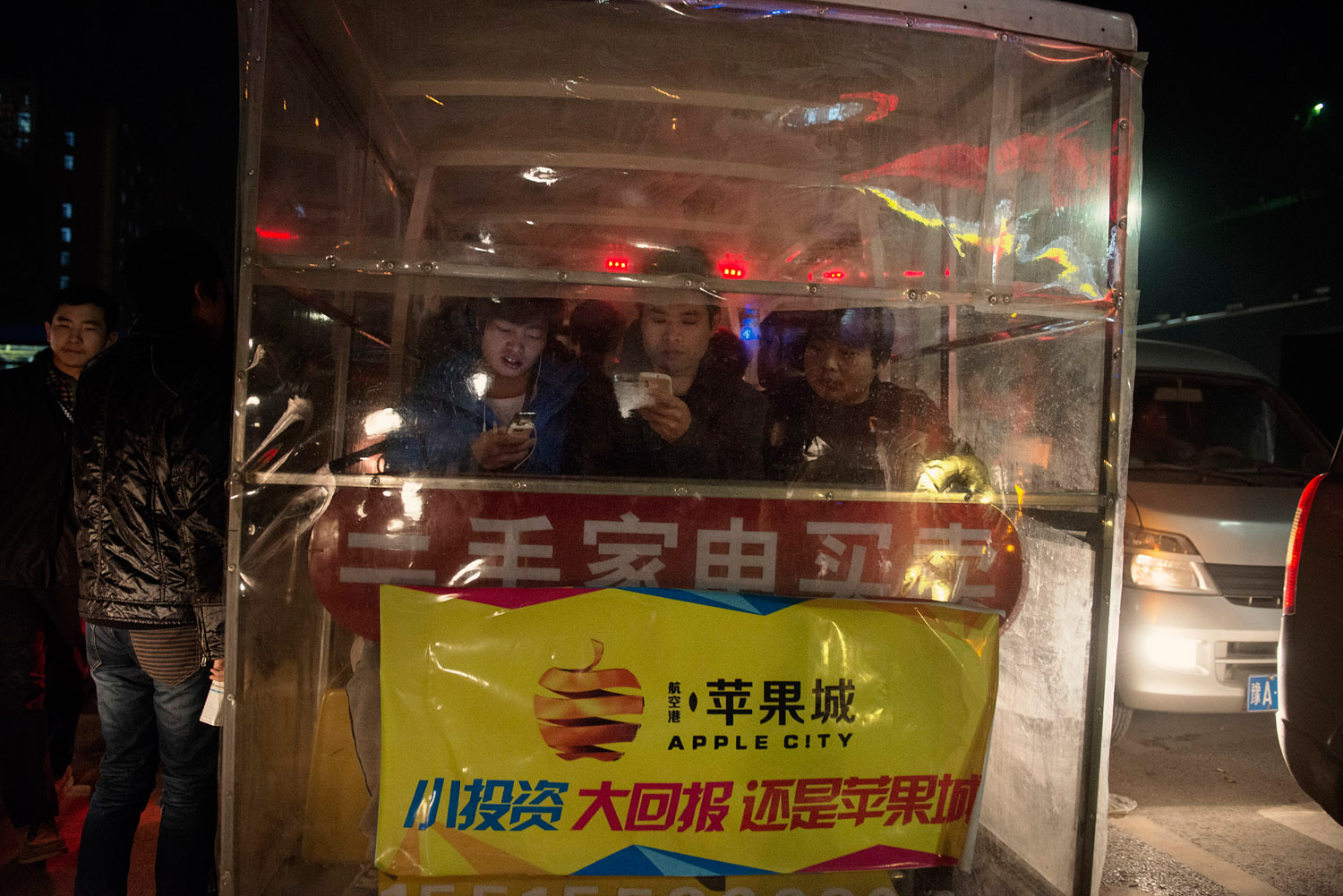 """Foxconn workers sitting in a cart taking them from the plant to the commercial/residential area of the factory town. On the cart a promotion for a housing project nicknamed """"Apple City""""."""
