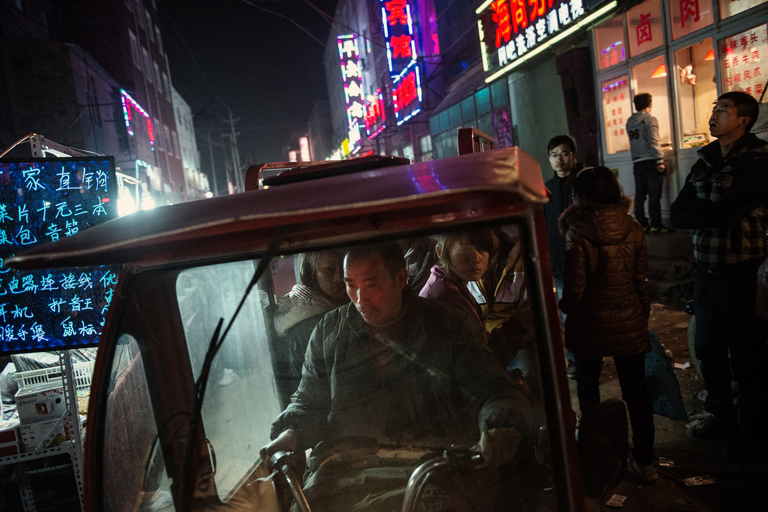 Foxconn workers sitting in a three-wheel taxi riding a dirt road of this factory town still in the making.
