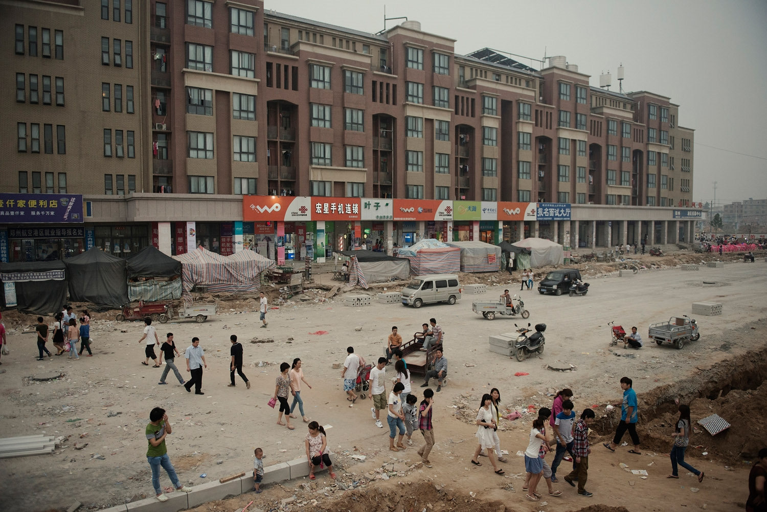 Foxconn dorms on a street still under construction.In the span of two years what were rural villages on the outskirt of Zhengzhou has become a bustling factory city dedicated to Foxcoon, and housing 200 000 workers. The city is still expanding with new factories being built.