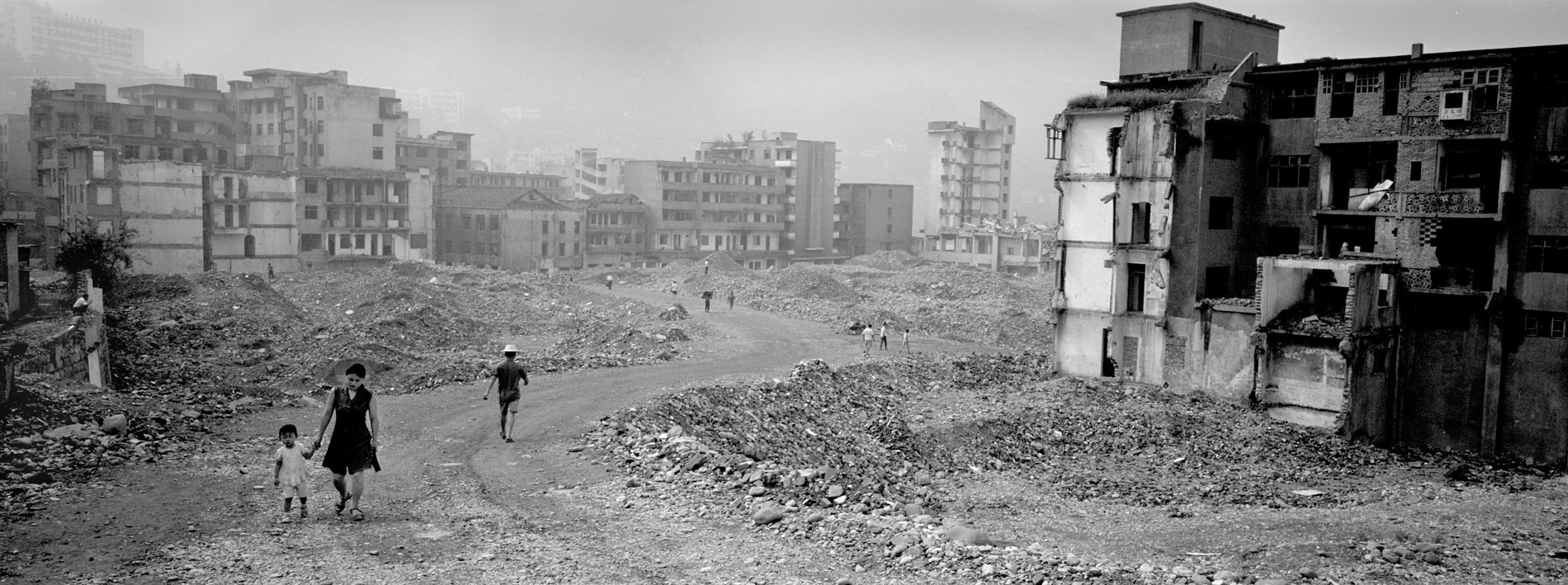 Inhabitants of Gaoyang walking by the razed buildings of the old city. Positionned by a subsidiary of the Yangtze, the city got flooded in the summer of 2006.