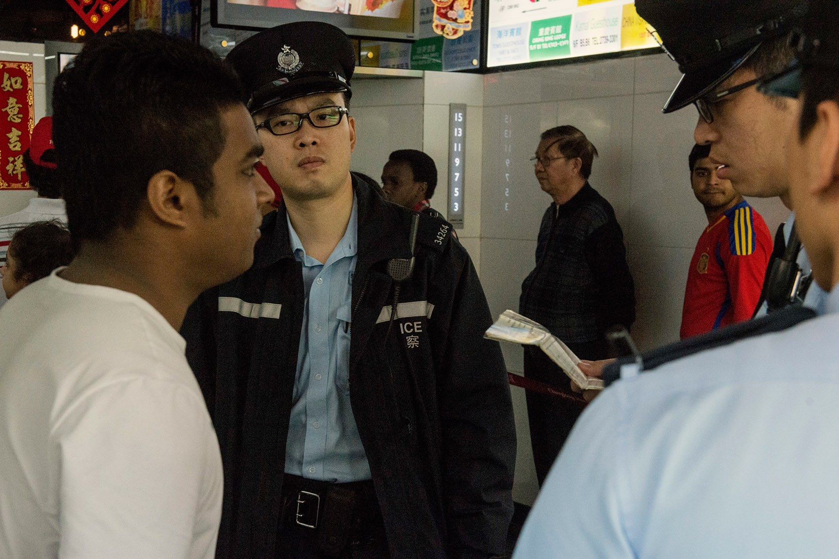 The Hong Kong police during an ID check at the Chungking Mansions. Such operations occur daily at the Mansions, where number of illegal immigrants reside. Many other residents or workers of the Mansions have applied for political asylum. However their application can take years to be processed during which they have no rights to work. Many do so but have to hide from the police.