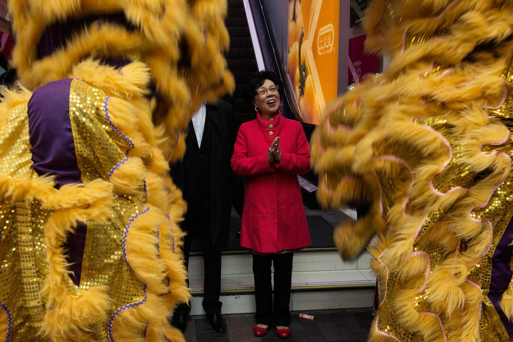 """Mrs Lam Wai Lung, Chairperson of the Incorporated Owners of the Chungking Mansions cheering at acrobats performing the """"good luck"""" lion dance, part of the Chinese New Year celebrations. Mrs Lam arrived in Hong Kong from Fujian province in Mainland China in 1979. After various factory jobs she set up a guest house in the Chungking Mansions. As Chairperson of the Mansions owners association she lead efforts to improve the business environment, including reduction of fire hazards, improvement of security through the installation of a network of CCTV cameras, building renovation and upgrade of the facilities such as the elevators..Some business owners complain the the association favors Chinese owners over South Indians."""