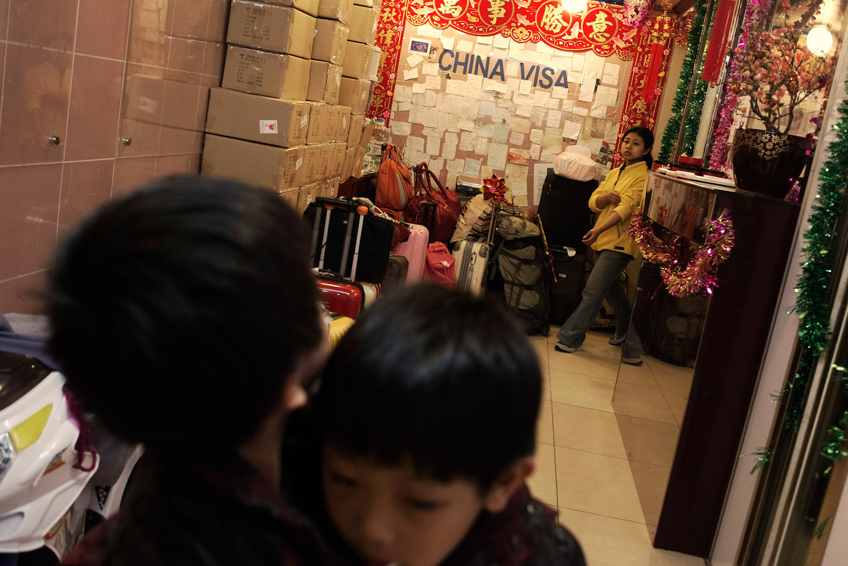 """Kids playing the lobby of a Chungking Mansions guest House. On its wall a """"china visa"""" sign and numerous notes left by guests seeking information, praising the guest house. Many travelers heading to China do a stopover in Hong Kong and stay at the Chungking Mansions where some cheap guest houses double as visa agency."""