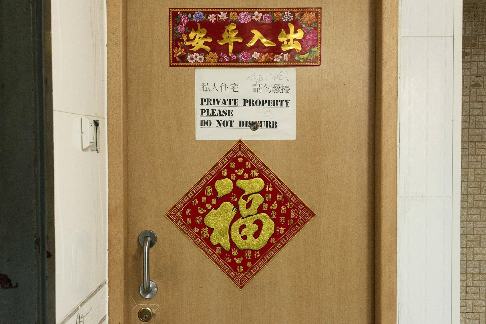 Inside the Chungking Mansions, the door of a private apartment where a Chinese family is living. Most of the residents of the Mansions are transient workers and hostels guests. However a few families live there in spite of the building bad reputation..