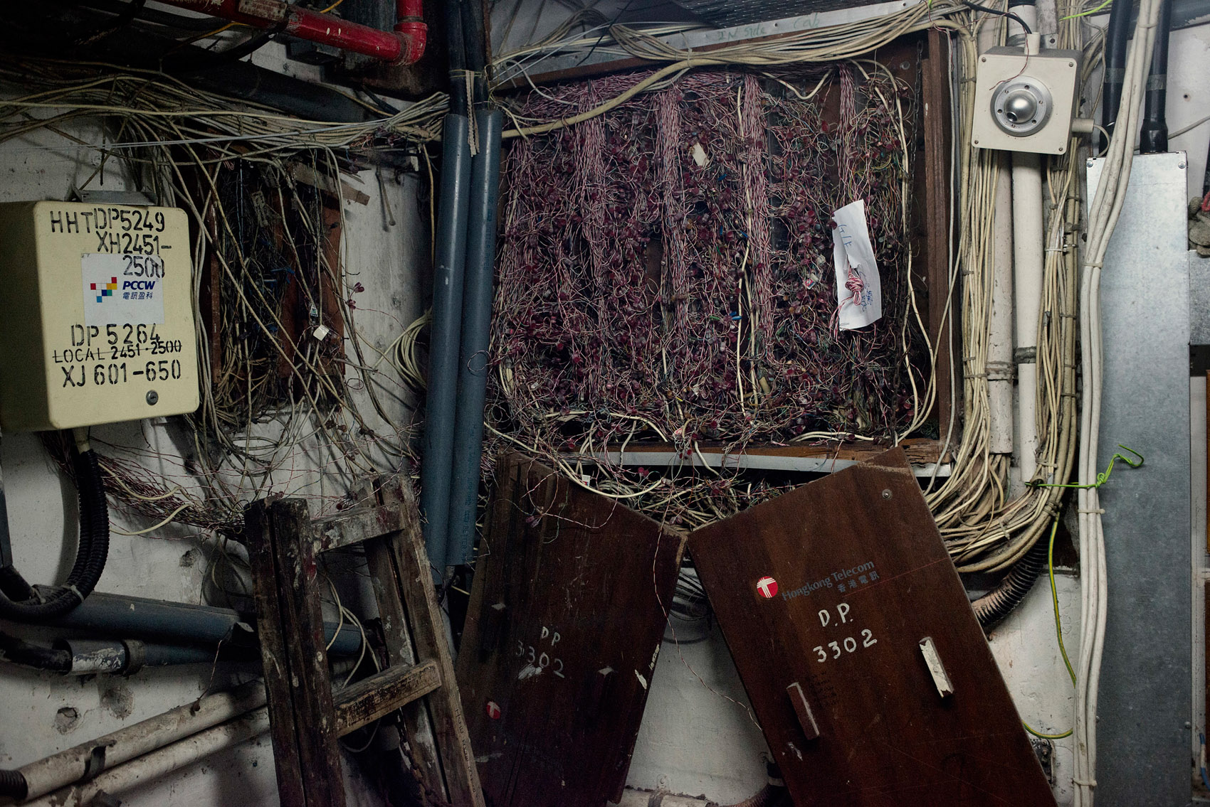 Phone and electric cables in the open in a staircase of the Chungking Mansions.