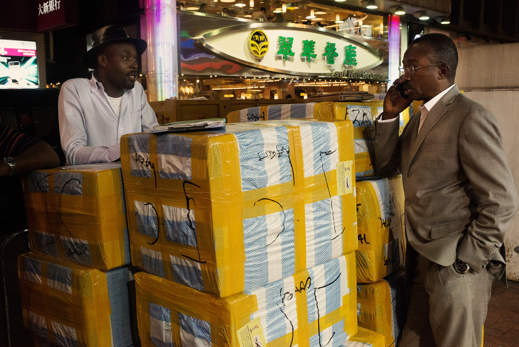 On a side street of the Chungking Mansions, Nigerian traders stand by boxes filled with mobile phones about to be shipped to Lagos. The trade in mobile phones accounts for a a large part of the business conducted in the Chungking Mansions.