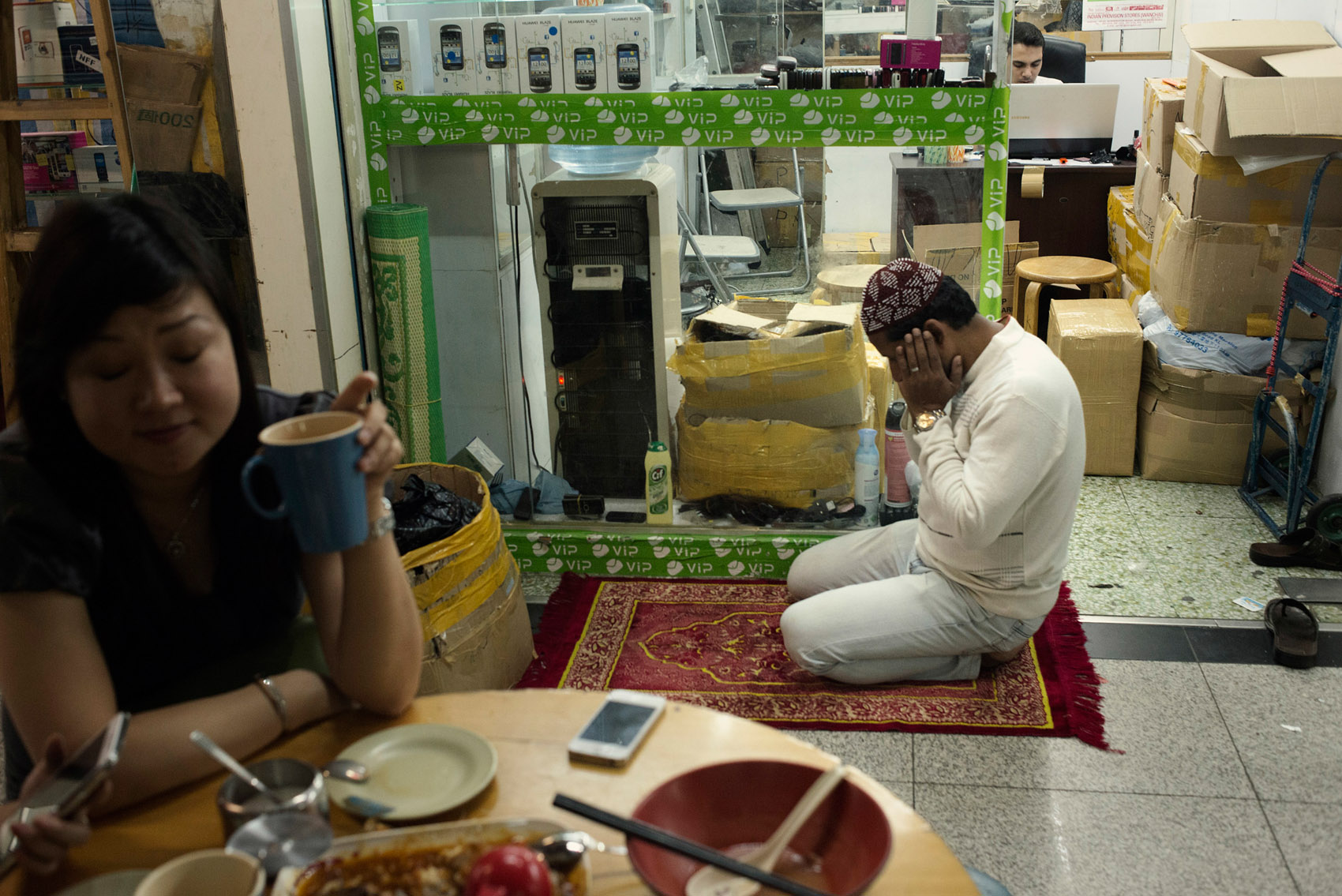 A Muslim trader inside kneeled for his evening prayer, in front of his store, next to mainland Chinese having dinner. Many of the businesses at the Chungking Mansions are ran by Muslims. They mostly go and pray at the nearby mosque on Nathan Road, the biggest in Hong Kong, but when they don't have time they will pray inside the Mansions.