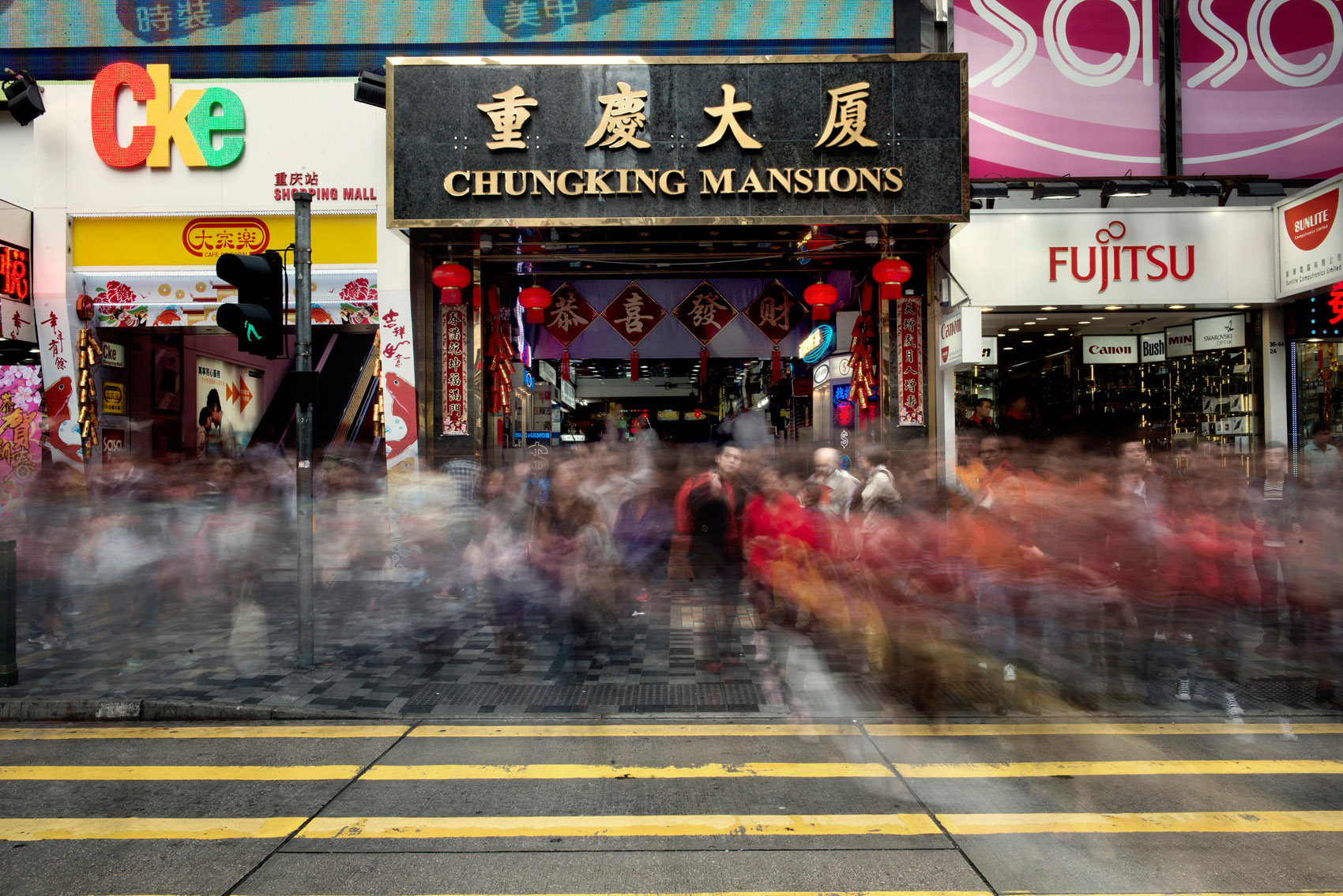 """Pedestrians walking in front of the Chungking Mansions. The Mansions are situated on Nathan Road also called the """"Golden Mile"""", a central street of Hong Kong heavy with traffic and popular with tourists. Stores lining Nathan Road make great business catering to the need of its crowds.."""