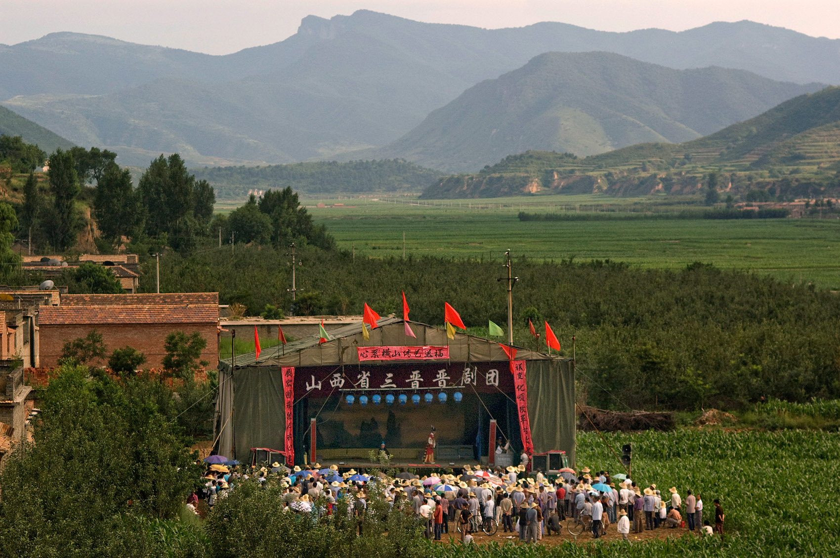 In the countryside the troupe has set up stage and is in front of an audience of peasants wearing straw hats.   Eight hours a day, seven days a week, Gao, Tianjun and their friends are on stage, impersonating Princes, Generals and Emperors. Keeping alive one of China greatest cultural heritage, its opera.Under scorching heat or freezing cold, they sing, dance and mime stories of love, wars and treason in front of a mesmerized audience of peasants. They go from villages to cities, year around, bringing with them stories of an ancient and long gone China. Their shiny and colorful clothes off, they live the low life, sleeping and eating on the floor, trying to make-do with the meager money earned from their skillful art.