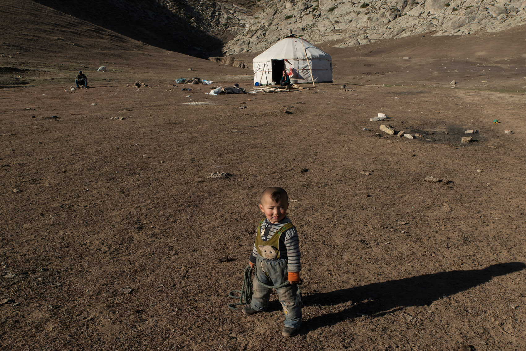 In the grassland of the Altai mountains, a young Kazakh nomad standing in front of the family yurt where both his parents stand, during the yearly migration from summer to winter pastures.