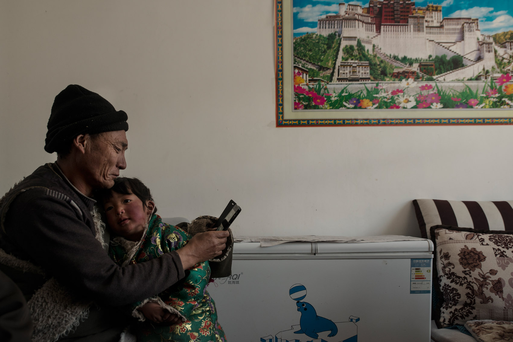A Tibetan nomad, holding his granddaughter in the house they recently moved in. They bought the house with government subsidies. Although featuring many amenities of modern living, satellite TV, washing machine, fridge..etc, the owners complain about the poor quality of the construction and point at many items already damaged just after a few weeks of occupancy. This former nomad has kept the family tent and plans to use it for a restaurant catering to tourists visiting the region. As nomads have to give up pastoralism, many see tourism as an alternative source of income.