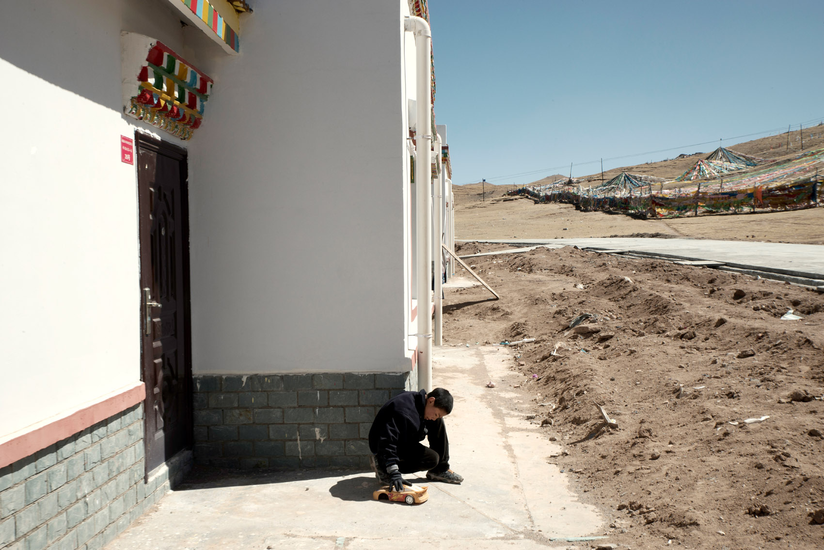 A Tibetan boy playing with a toy next to an empty home part of a recently built housing project for relocated Tibetan nomads in Madoi (Qinghai).