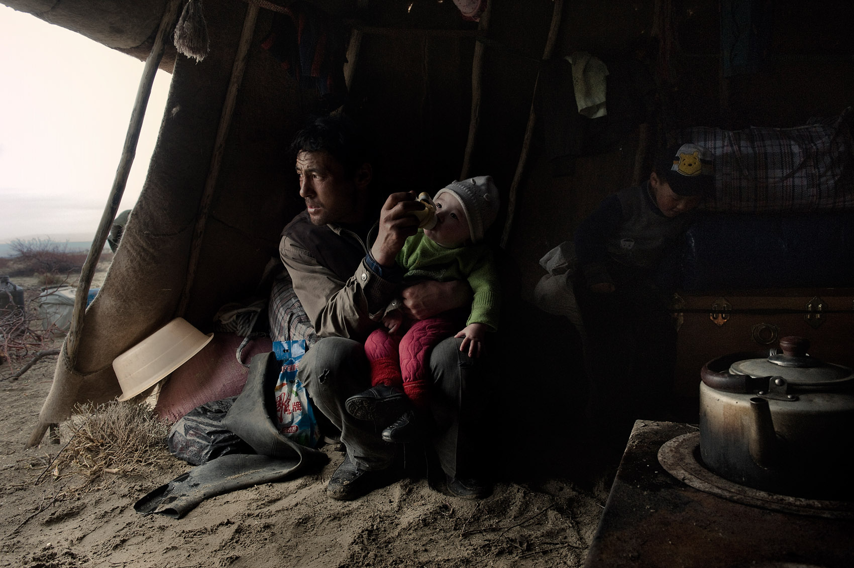 Near Buerqin (Xinjiang), in his tent, a Kazakh nomad feeding his 9 months old daughter, next to his son. Some in his extended family have moved to nearby Kazakhstan, as they were forced to sell their herd. The family owns a dozen camels, 25 cows and a hundred sheep and earns between RMB 10 000 and 25 000 ($ 4000)a year. They are thinking of leaving Xinjiang for Kazakhstan.