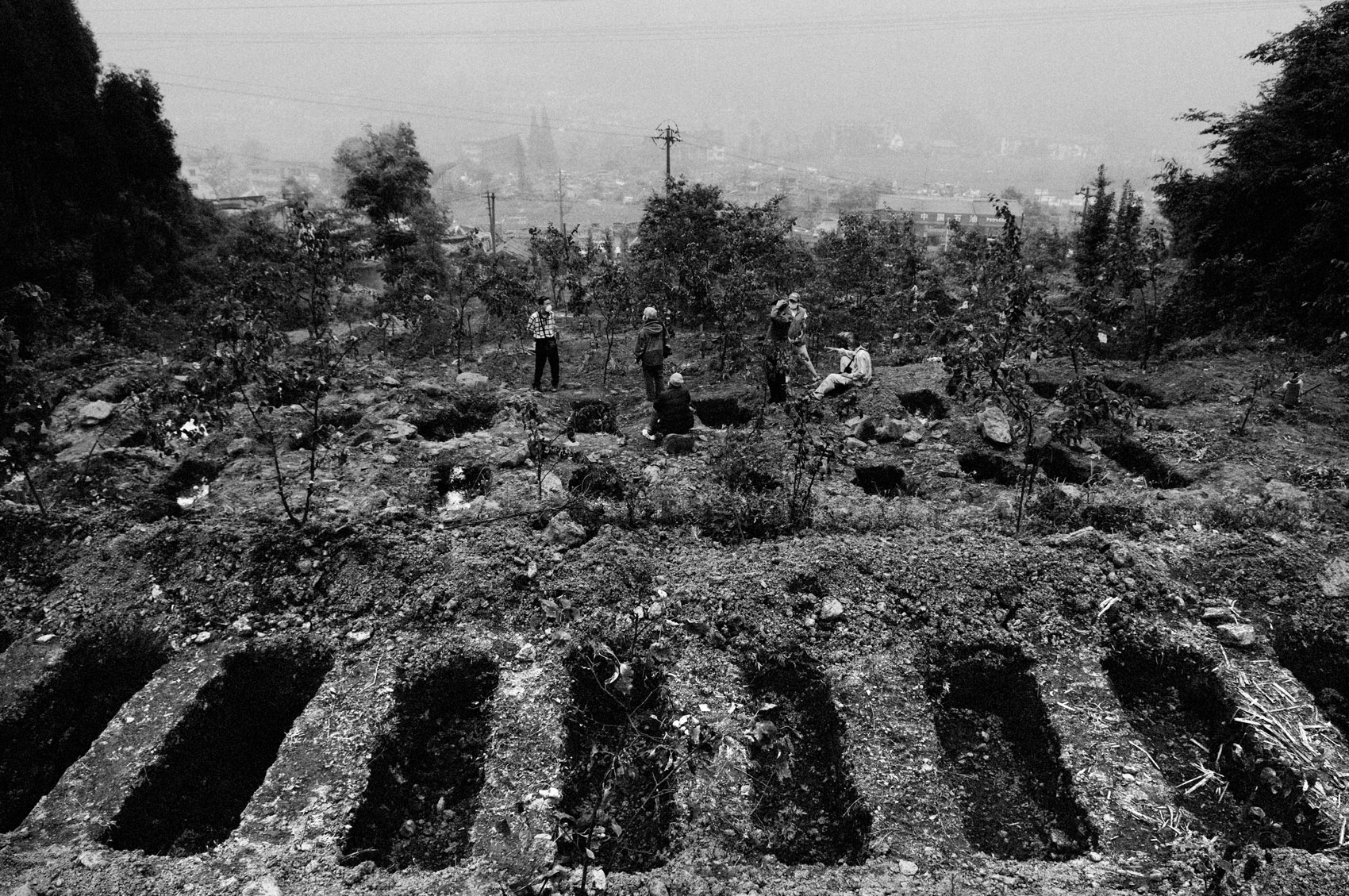 To bury the many victims of Hongbai, soldiers have digged graves on the hills overlooking the city.