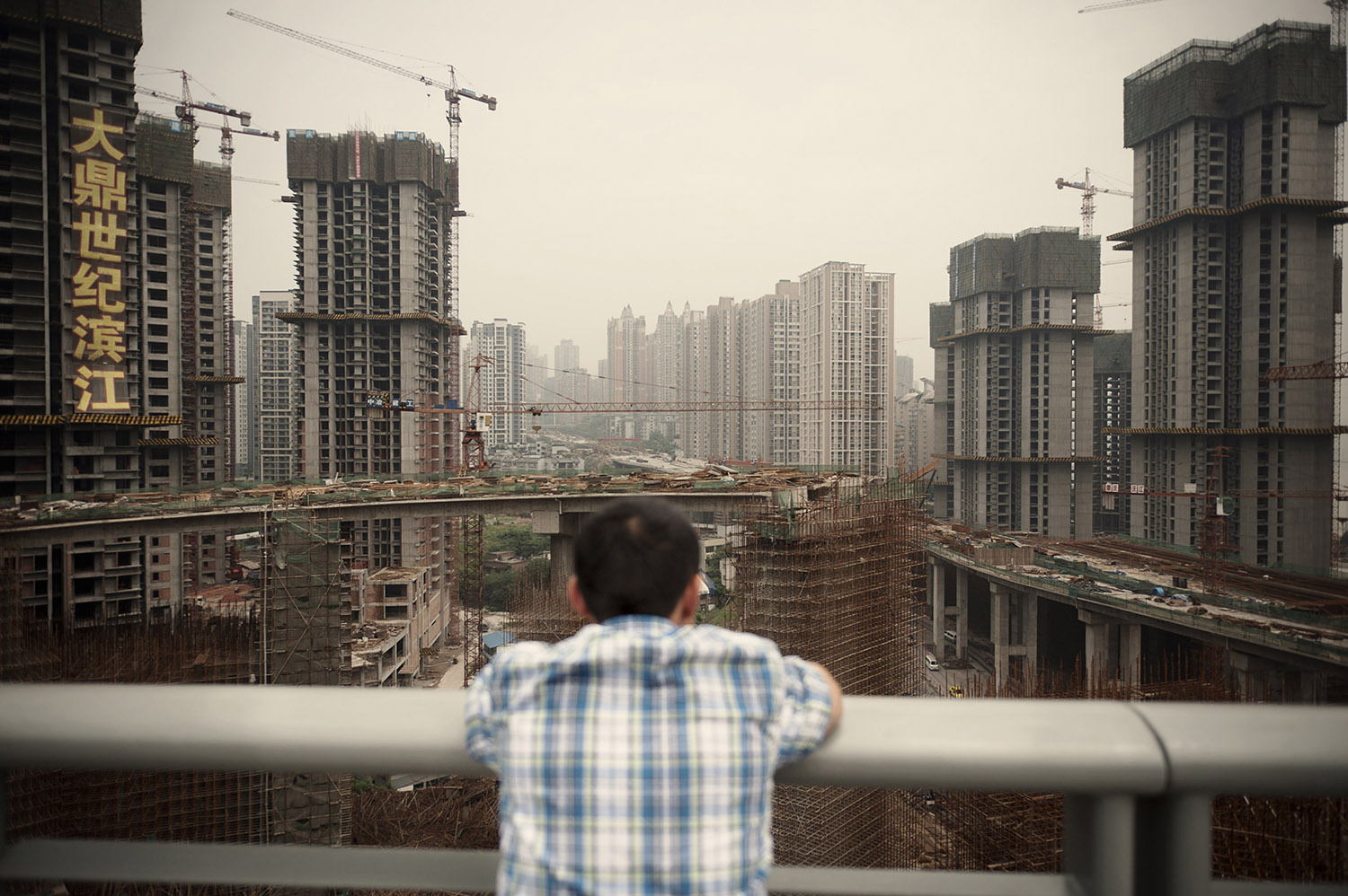 "A man staring at a large residential complex under construction by the Yangtze in Chongqing. Part of the ""Chongqing Model"" developed by Party Secretary Bo Xilai includes the construction of social housing. Chongqing has the fastest growing GDP in China. R esidential housing investment as a share of China's GDP has tripled from 2% in 2000 to 6% in 2011."