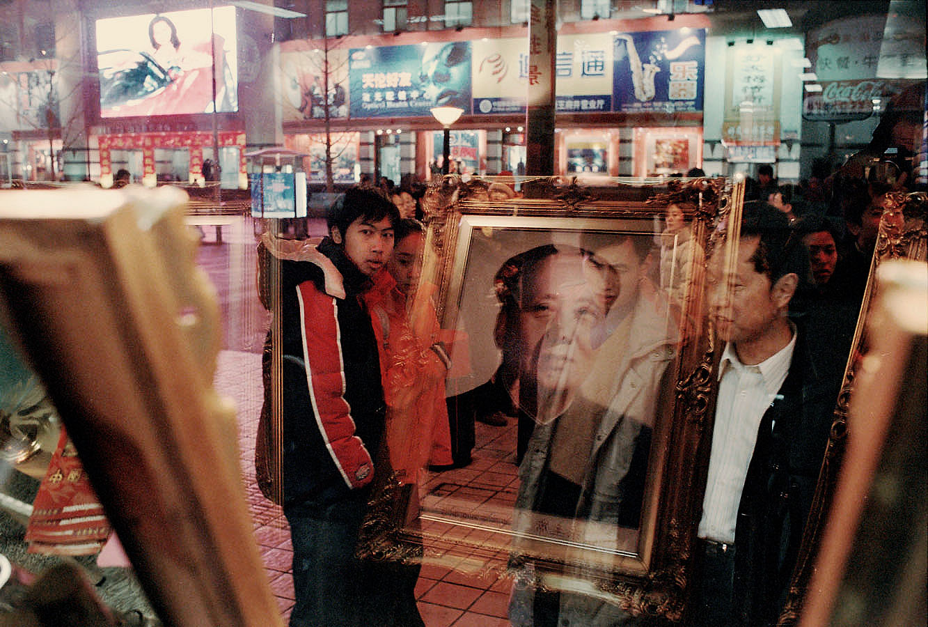 Portraits of Mao refelcts in the window of a photographer store in a commercial artery of Beijing.