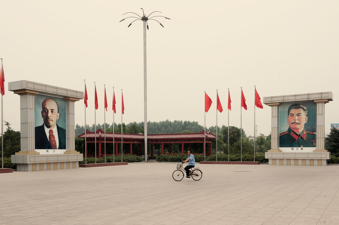 On The East is Red square of, a local riding his bike by giant portraits of Lenin and Stalin..
