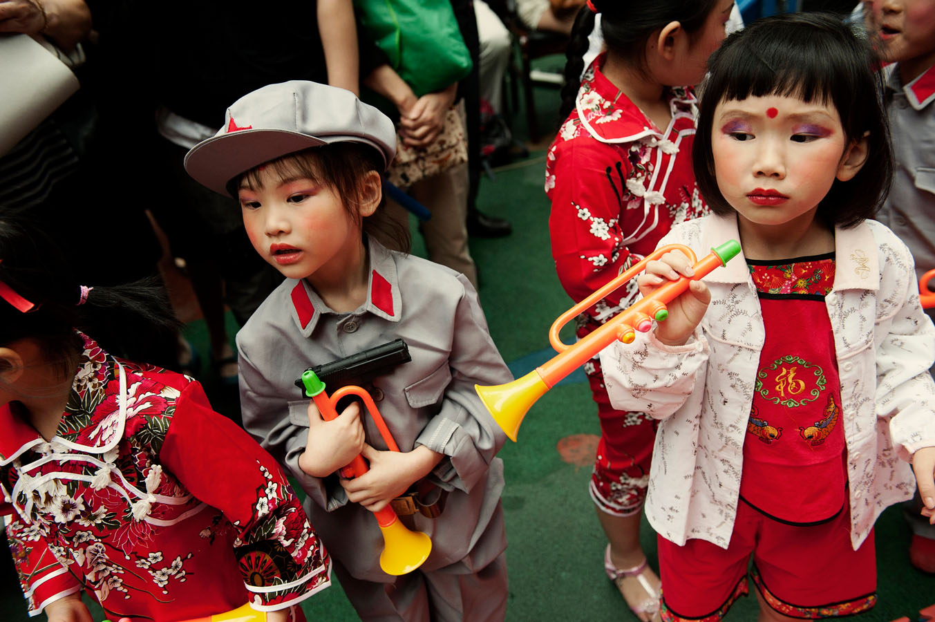 At Dadi kindergarten in Chongqing, children before a show for Children's day. One of them dressed up as a PLA soldiers is holding a plastic gun. The show includes a revolutionary piece: the story of Wang Erxiao a kid who sacrifices himself to lead the 8 route army to victory against the Japanese.