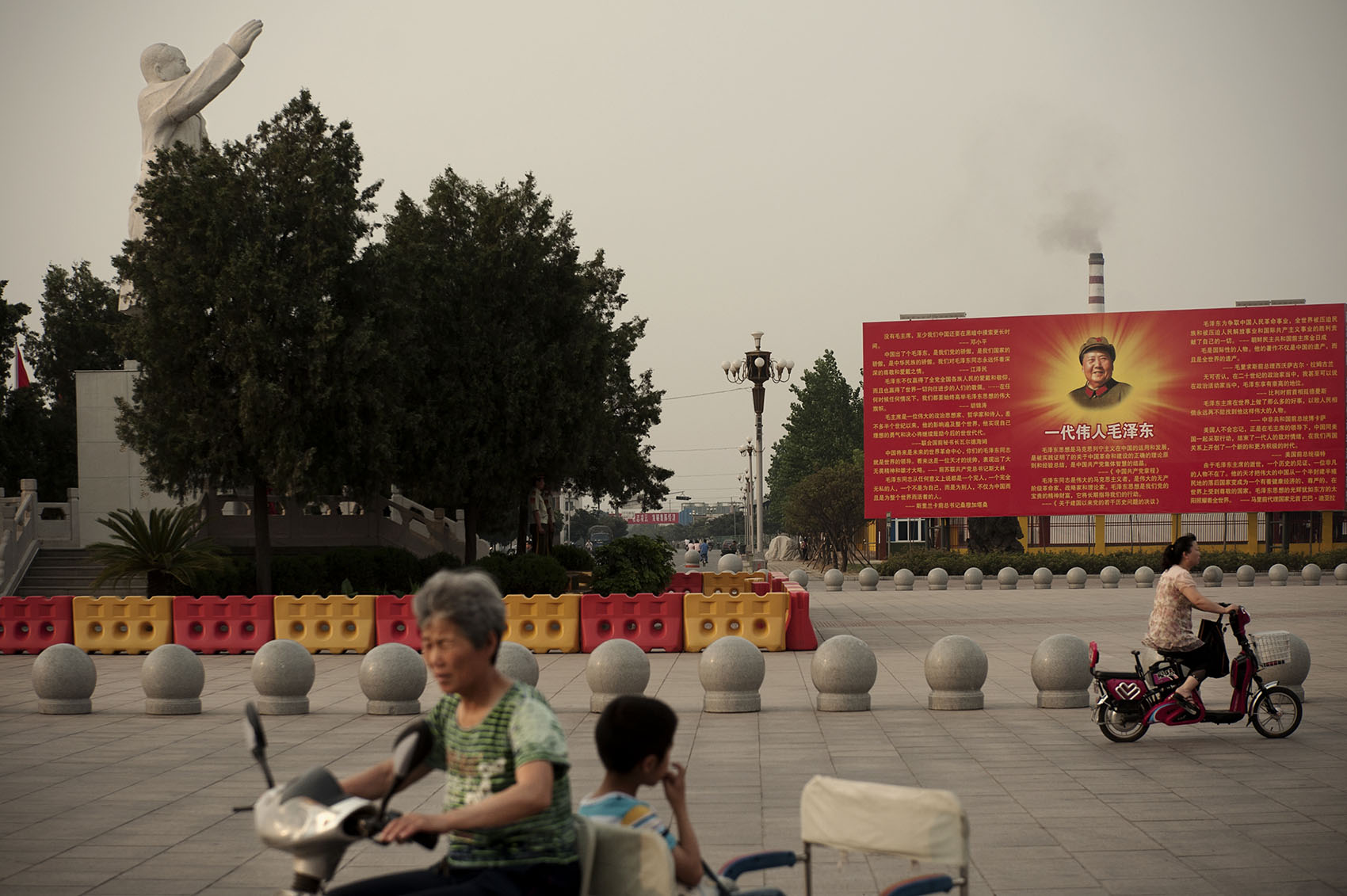 In Nanjie village, locals riding their electric bikes on the East is Red square where a statue of Mao stands his right arm raised heavenward. Nanjie in Henan Province still works as a commune. The city's Party Secretary wants Nanjie to stay true to Mao's communist ideology.