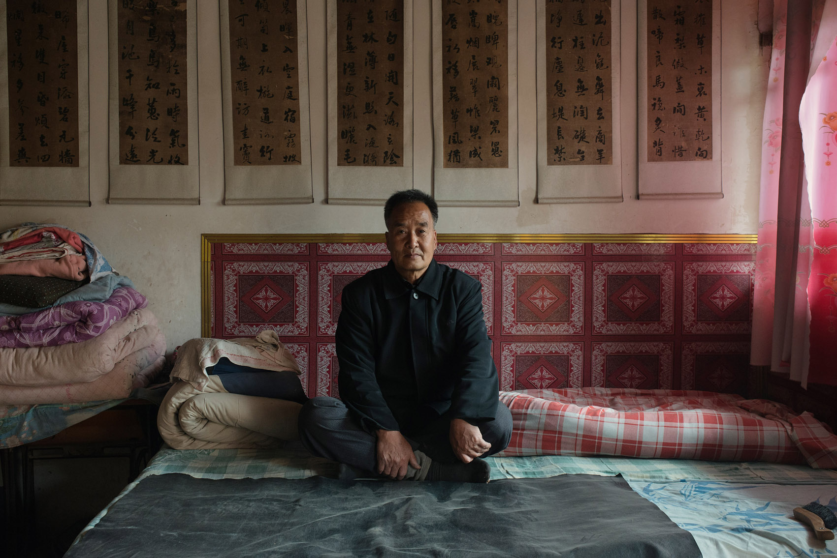 Changjiahe village  65 years old,Niu Wenxuan, Besides farming, Niu has a passion for calligraphy and he occasionally does restoration of old scrolls. The scrolls hanging above his kang date back from the Qing Dynasty.
