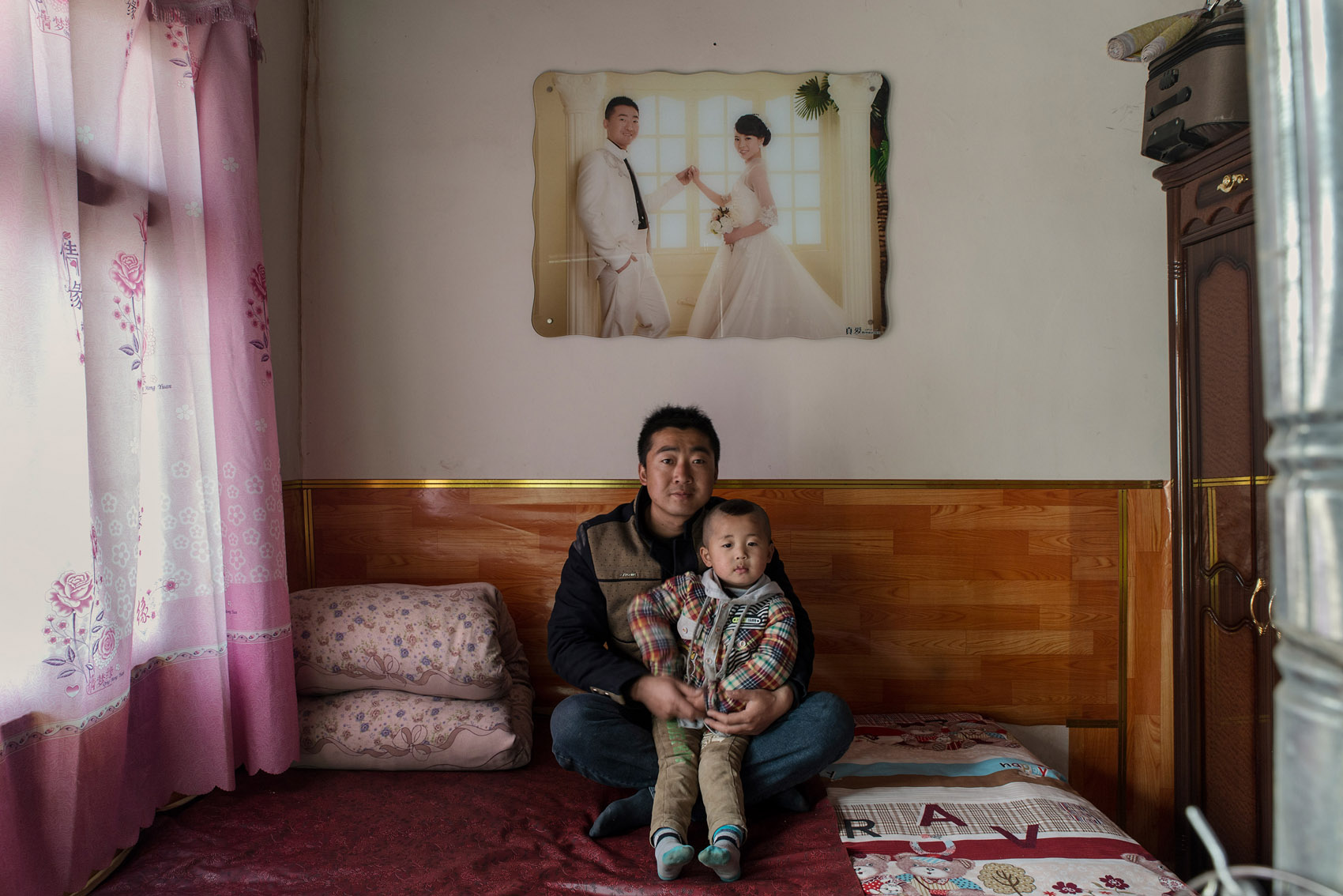 Anyuan Village  32 years old Niu Binggui, with his three years old son Niu Haoran Niu Binggui is a cook for a construction company in Ningxia province several hundredkilometers away from the family hometown. He is now is own boss in charge of the catering for aconstruction site. It means a little more money but also more responsibilities. For 10 years he has been working as a cook in restaurants and dreams of opening his own, but lacks the funds to do so.  In two day he will be leaving for work at the end of his new year break. He won't see his family again before months.