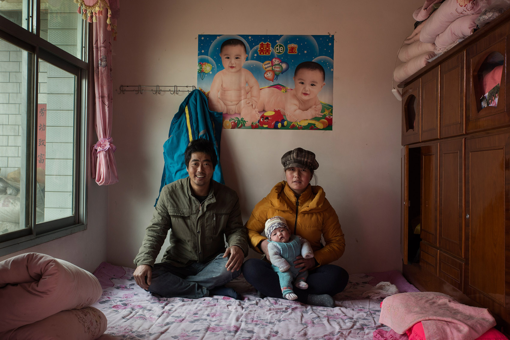 Anjiawan village  Peng Yongjie, 38 yo, with his wife 30 years old Di Jinfang and their 40 days old daughter.  Peng And Di have been trying to have a baby since they got married 8 years ago. They have soughthelp from local private clinics with no success and at mounting costs. Eventuallythey went toa hospital in the provincial capital Xian, where they were quoted20,000RMB (US$ 3,200)for anartificial insemination. At the time Peng and Di only had 3,000 RMBin savings. For four years Peng and Di saved money to eventually be able to pay for the operation last year. The first attempt was successful. They now want to have another baby, a boy. The poster on the wall was put up 7 years ago.  Peng is a construction worker and makes about 100 CNY (16US$) a day. The picture was taken the day before Peng's departure for work after the Chinese New Year break.