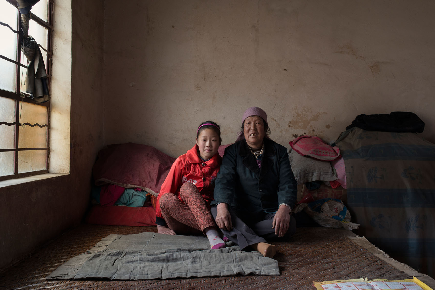 Shanmen Village Jin Fener, (63) with her granddaughterMa Xiyang, (12). Xiyang's fatheris mentally ill and recently cracked his skull open in a bad fall. He has been bedridden for a month. She has to look after both of them with barely any income. Her husband was away spraying pesticides in their fields, half an hour away from the village. They also produce a bit of honey (30 yuan / jin)
