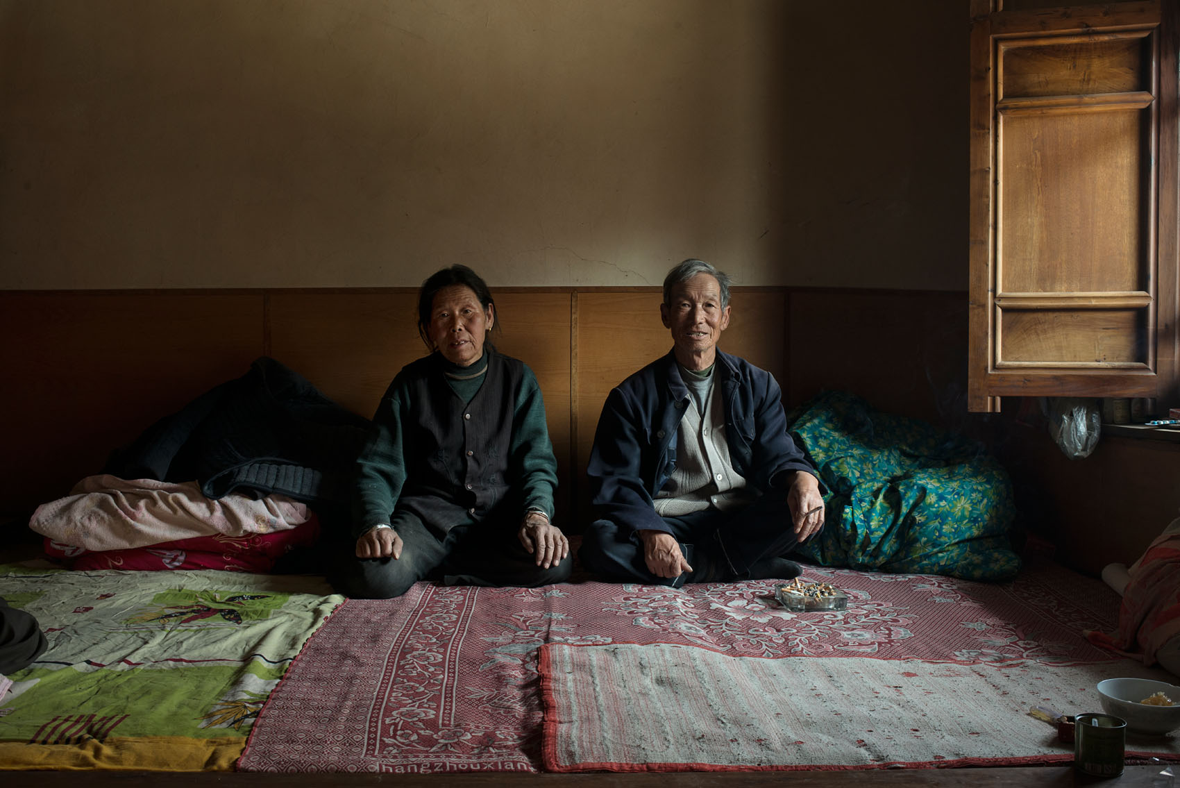 Yujiaping Village Yu Zhanglai (67) with his wife Dong Juming (67).  60% of the population of Yu Jiaping has moved down to the new village but a new house costs 200K RMB (32,000 US$) and they can't afford to move. A new road has been built between the old and the new village. Each family contributed 1,000R RMB to the construction but they are too poor to contribute.