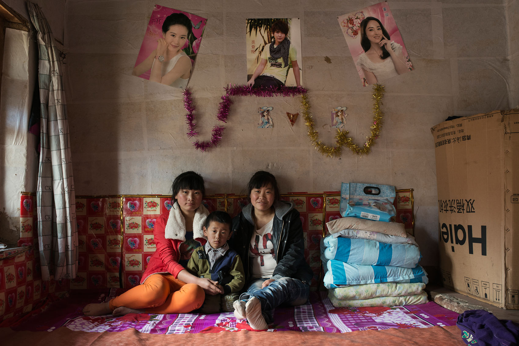 Jinshan Village From left to right : Wang Yandi (16) Wang Lei (5) Wang Yanxia (21) Lei'smother is working over a thousand kilometers awayin a supermarket in Xinjiang where the wages are higher.Yandi & Yanxia, two sisters,are taking care of their little nephew. They are on their own as their parents have passed away.  They will soon move to a new house the family is having built nearby.