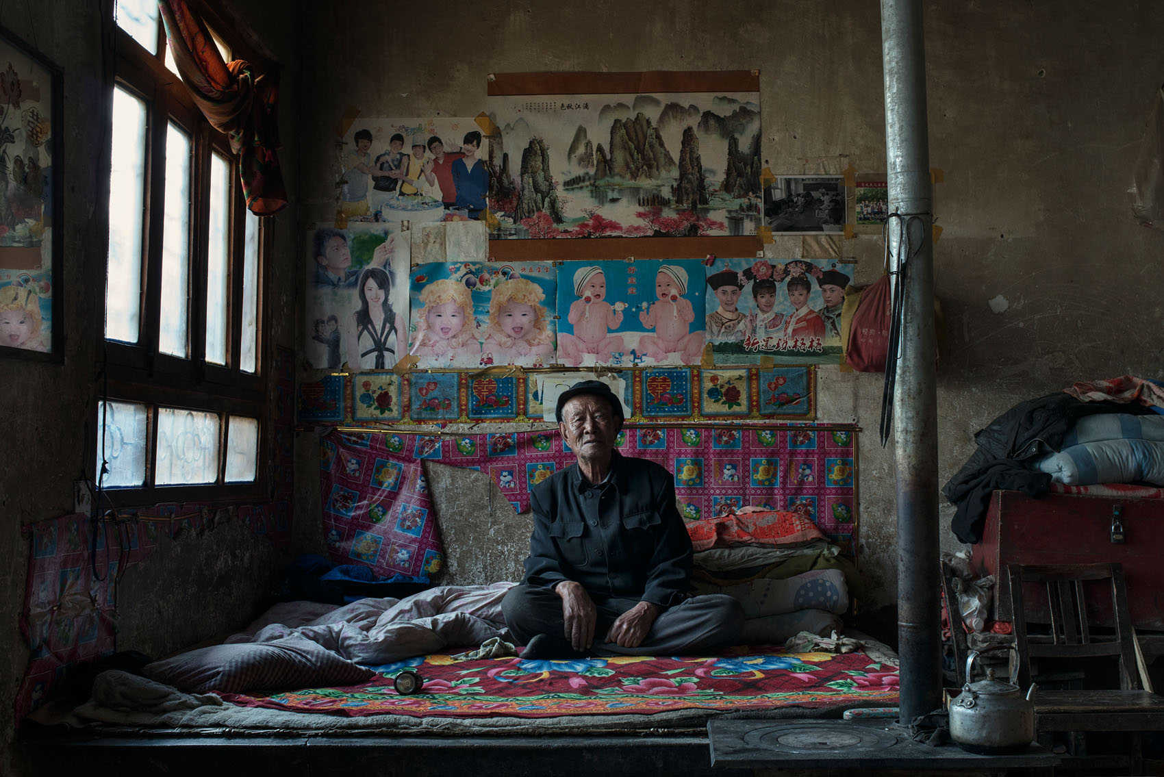 Huangmen Village Zhang Guizi(71) In his home, Zhang has a huge poster of Mao. Even though he complains about the destruction of the local Taoist Temple during the cultural revolution, he worships Mao who he says got his family out of poverty. Before the revolution they were living in a cave with no land of their own.They had to rent half a mu from the temple to be able to farm and had to give back a share of their crops in return. After the Liberation, they were given two mu and a cow but it wasn't until the Cultural Revolution that they didn't have to share their crops with the temple. In the 80's a fake Taoist monk came to live in the temple and was living off the locals' credulity. He died 4 years ago and now the Temple has just been renovated with financial contribution from all villagers. Zhang says it's nowhere near as beautifulas it was before, with poorly made statues and drawings but he is still happy to see it alive again.