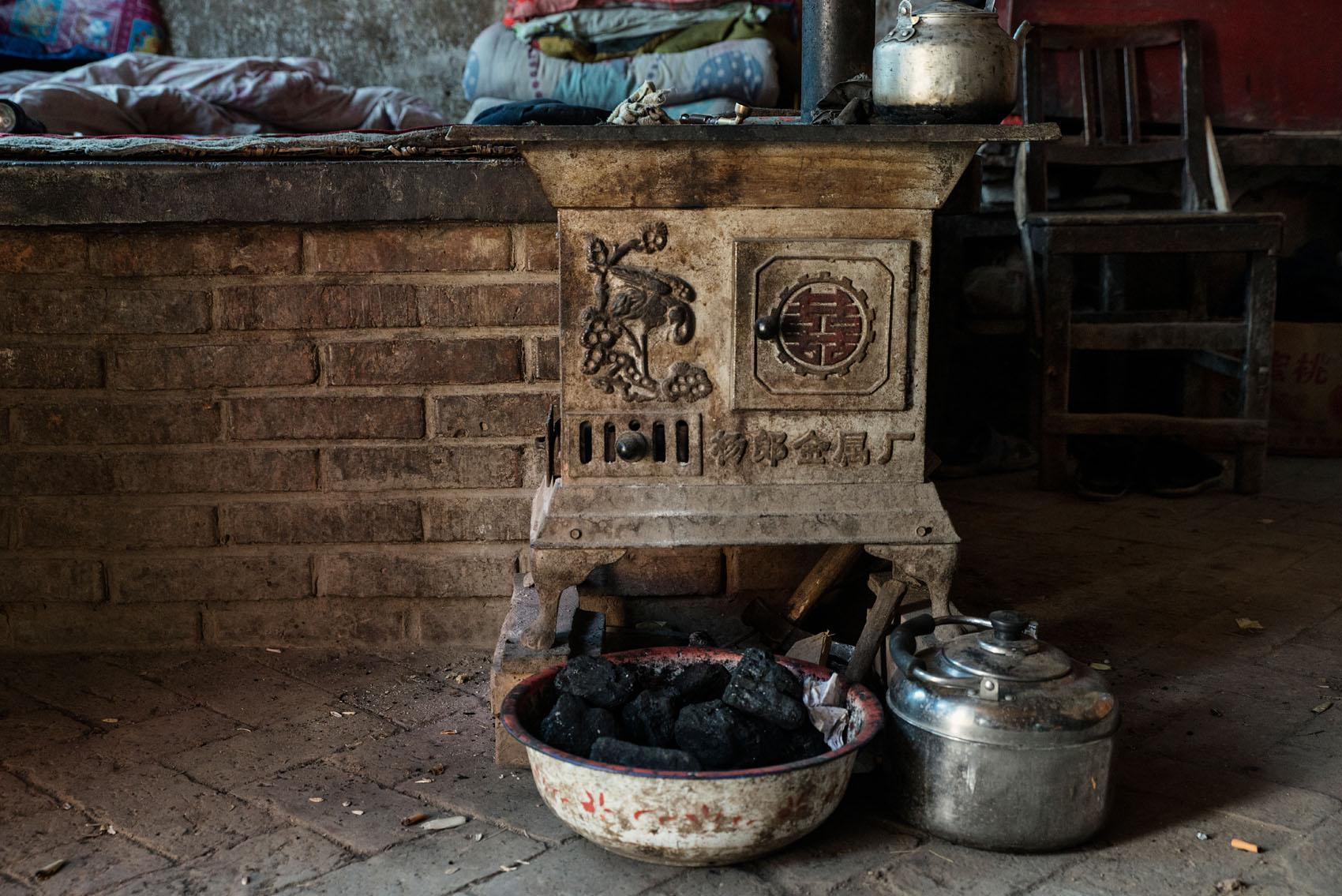 The coal burning stove next to Zhang's kang.