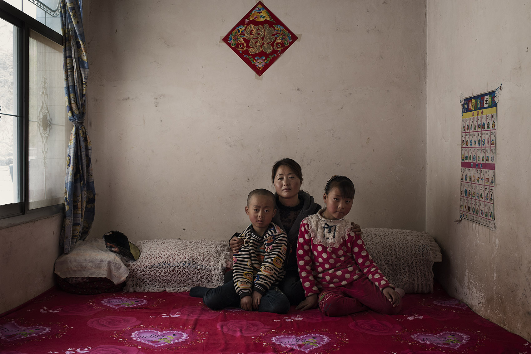 Jinshan Village Chen Xiuling (32) years old with her two children He Yawen (9) and He Guanghui (6) Chen's husband is a migrant worker in the South of Gansu 4 hours by bus from the family home. He sets up electric lines in the countryside and comes back home every two months. They builta new house a year ago. She says the old house was warmer (the old house was made of adobe while the new one has concrete floors and walls)but she is still happy with the new one. The construction of the house is not finished so for now they areliving in the smaller room. She met her husband in Lanzhou (the capital city of Gansu province) where they were both migrant workers. She subsequently moved to her husband's village where she is taking care of theirchildren.