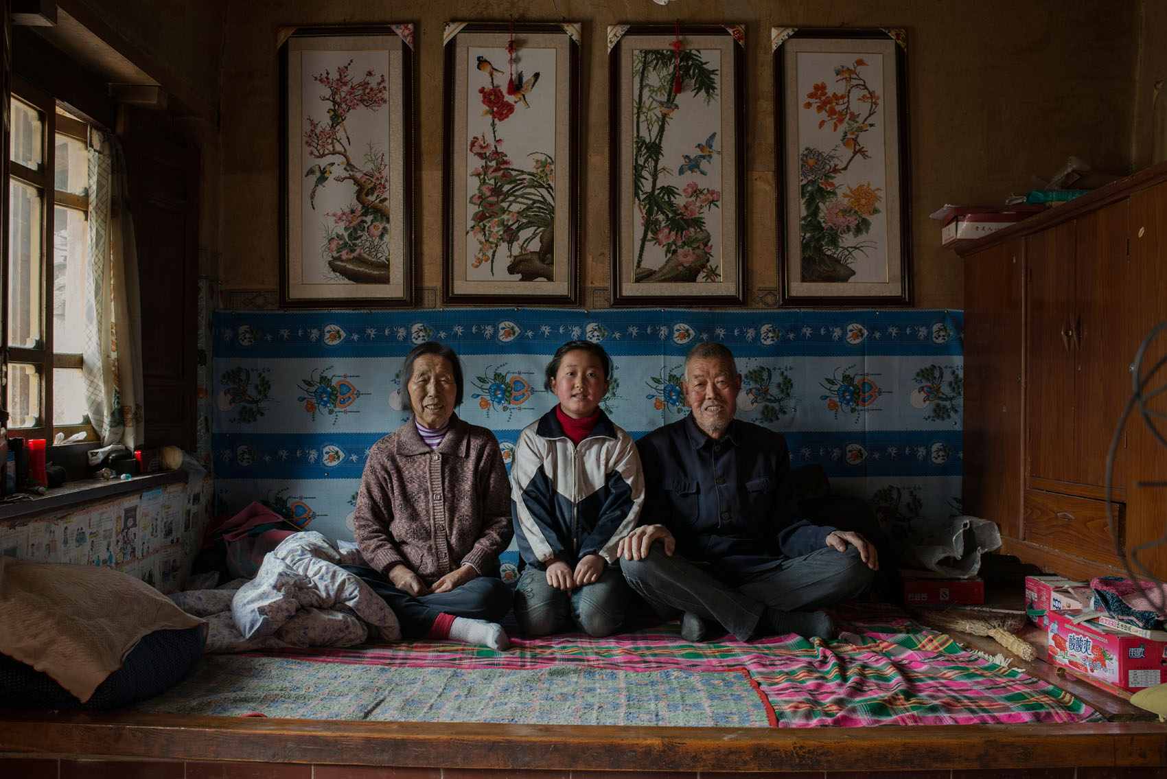 """Jingshan Village  12 years old Xie Hong with her grandparents who are taking care of her. Hong's mum left her after the death of her father (often widows don't stay with in-laws in poor rural China, even at the cost of leaving the children behind). Hong's grandparents are afflicted by heart diseases and the bills pile up, straining the household meagre incomes. Hong says she wants to study to become a doctor """"to take care of my grandparents, too often sick"""".  The frames above the kang are embroidery made by Hong's grandmother. Embroidery patterns and frames are sold at local markets and are popular home decoration in this part of China."""
