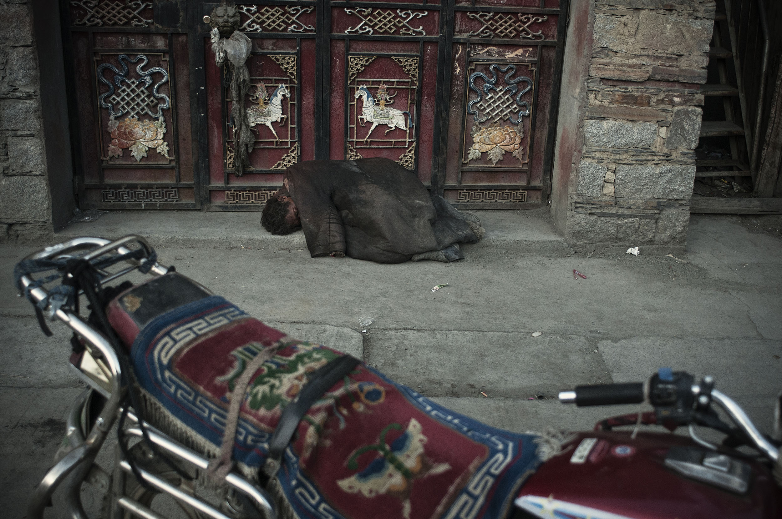 In Tagong (Sichuan) a beggar sleeping on the street in spite of sub freezing temperatures. The government policy of resettling the nomads is a threat to their livelihood. Most of them, with no education, and ill prepared for life in the city are unable to generate alternate source of income. Many of them live on government subsidies or compensations initially provided to them. When these dry up they are left with no way to support themselves.