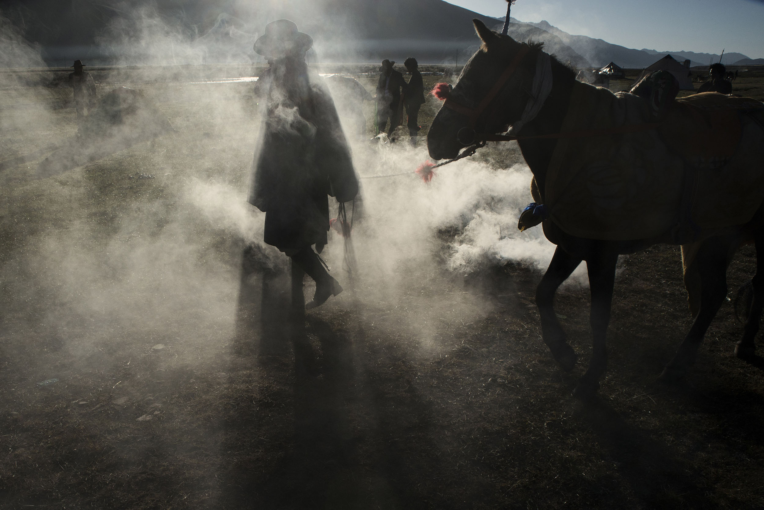 At sunrise, a Tibetan horseman walks his horse through the smoke coming from a juniper fire, a cleansing and strengthening ritual, before taking part in a horse race at Yushu horse festival. Nomadism is a pillar of Tibetan culture. The governement resettlement policy put this culture at risk as thousands of former nomads are forced into a sedentary lifestyle for which they are ill-equipped.