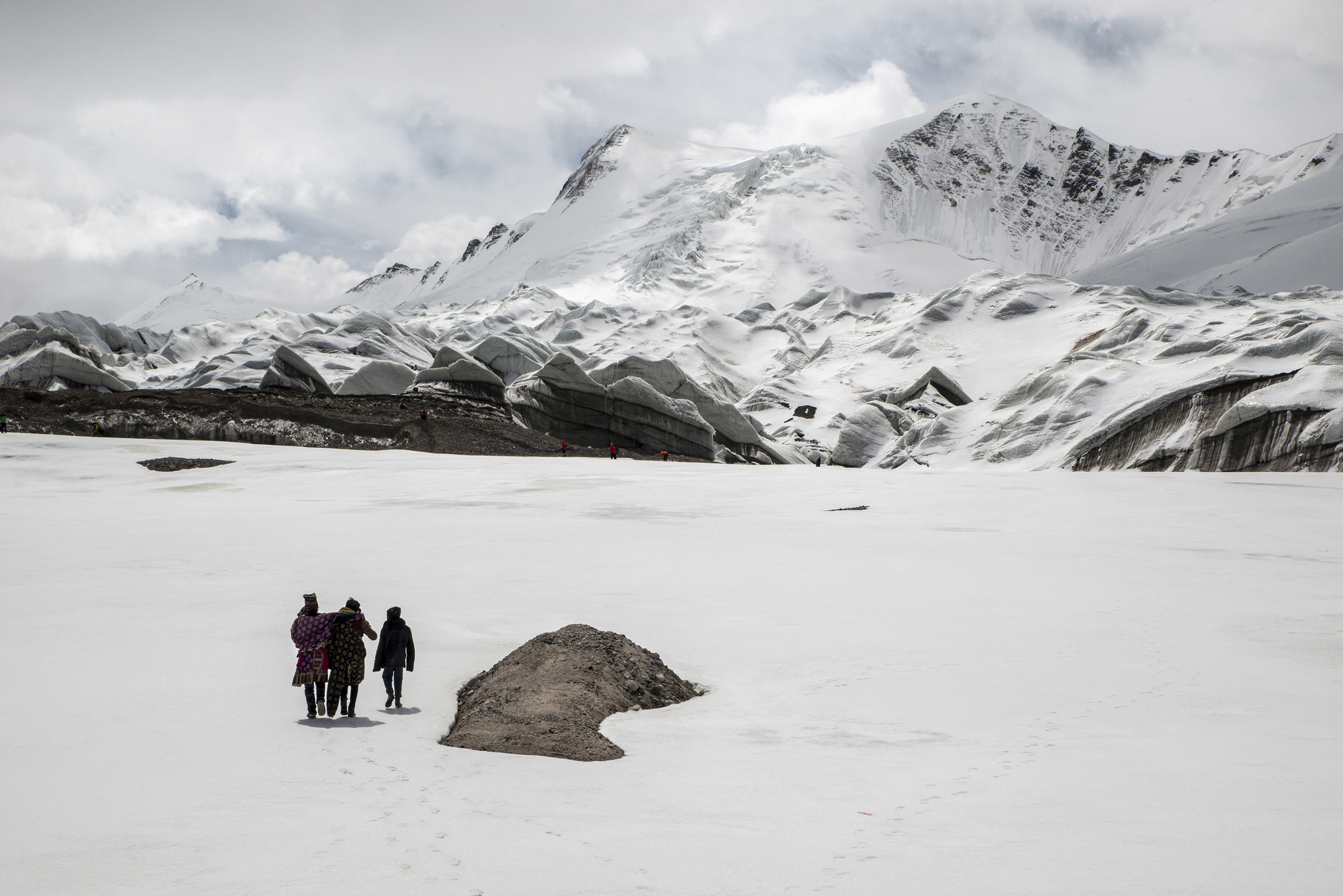 Young Tibetan nomads walking towards the Jianggendiru glacier source of the Yangtze river, in one of the most desolate and remote region of the Tibetan plateau. In large parts of the region, the Three Rivers Natural Reserve, grazing has been banned in the name of environmental protection while heavily polluting mining operations have been authorized.