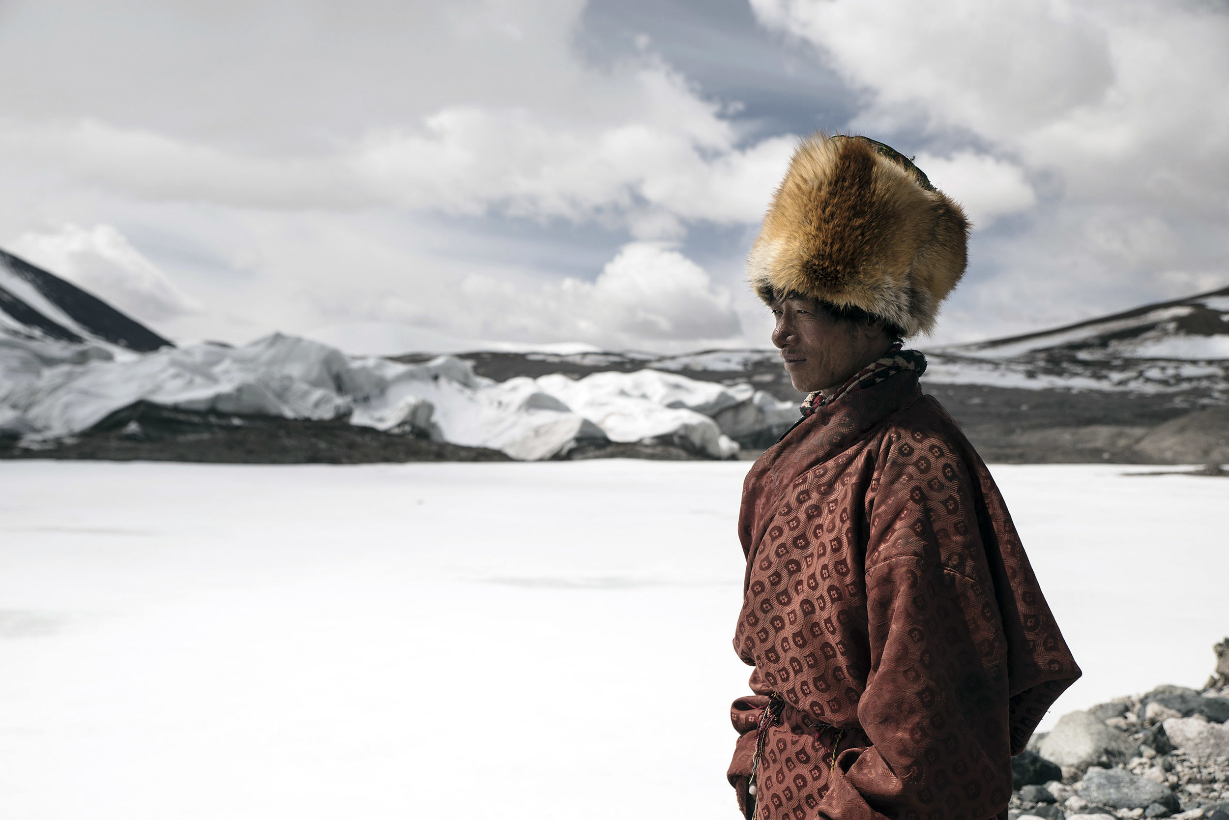A nomad wearing a hat made of fox fur, at the sources of the Yangtze river where he and his family live year around which was impossible just a few years ago. Rising temperatures and receding glaciers allow yaks to graze in the area.